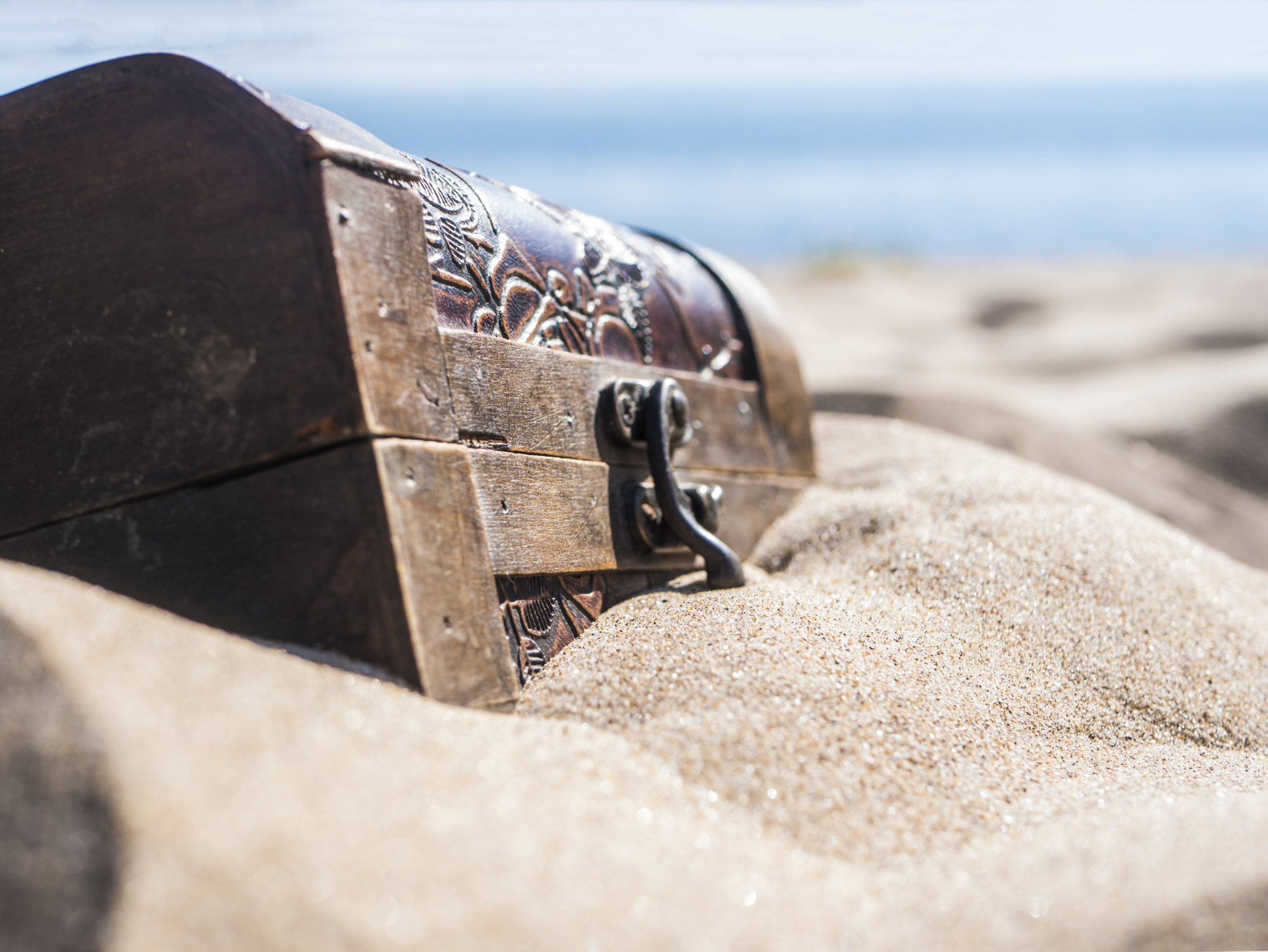 A treasure chest peeking up out of the sand.
