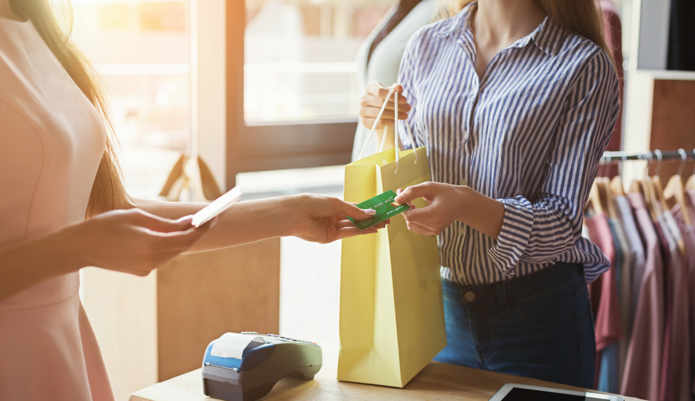 Woman with shopping bag handing boutique clerk credit card.