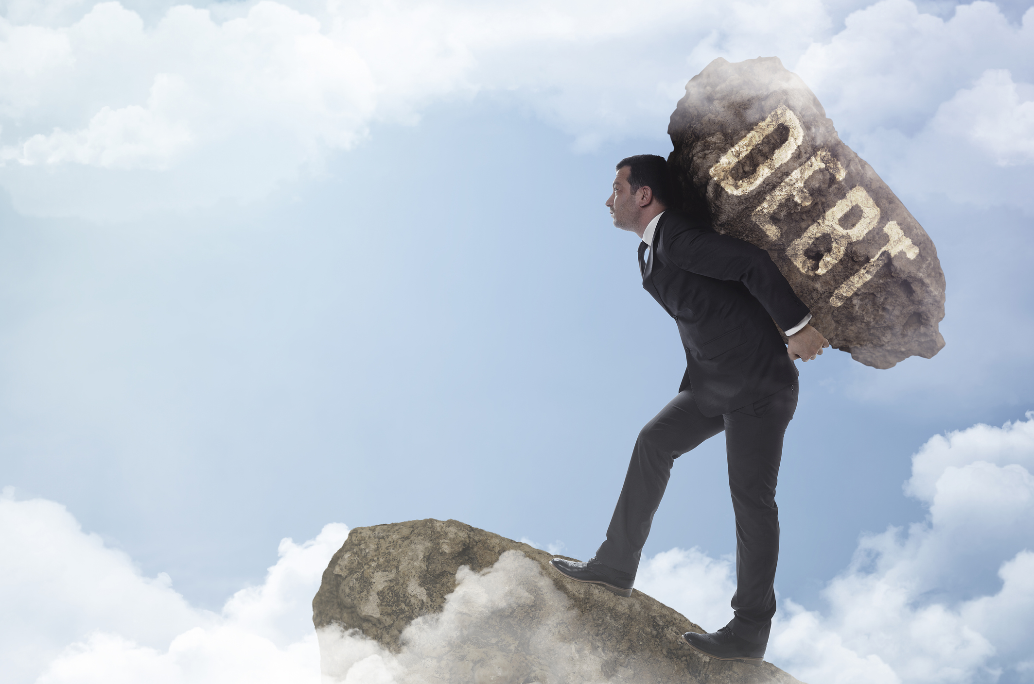 Man in suit carrying boulder labeled DEBT to edge of cloudy precipice.