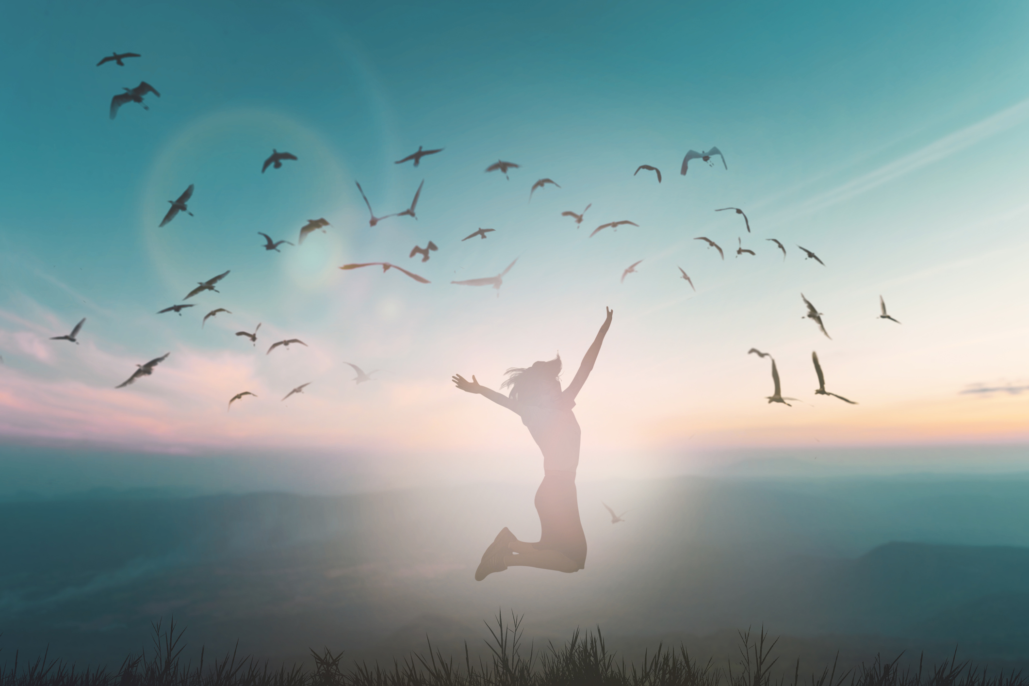Silhouette of woman leaping freely in meadow amid flock of birds.