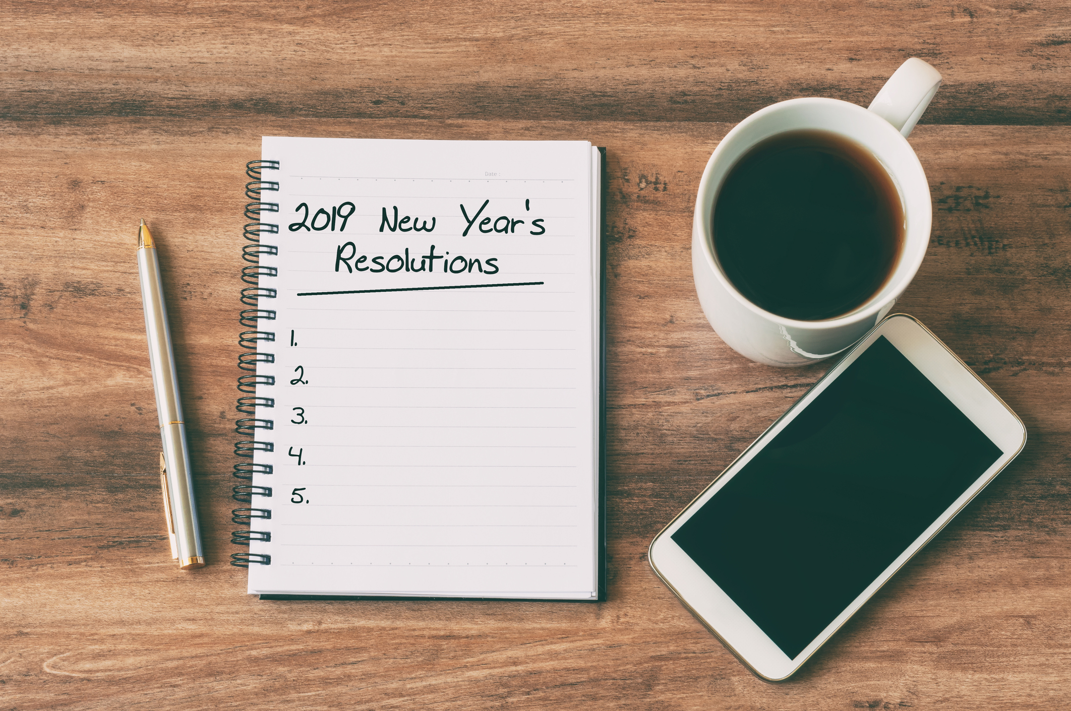 A coffee and cellphone next to an open notebook that read 2019 New Year's Resolutions.