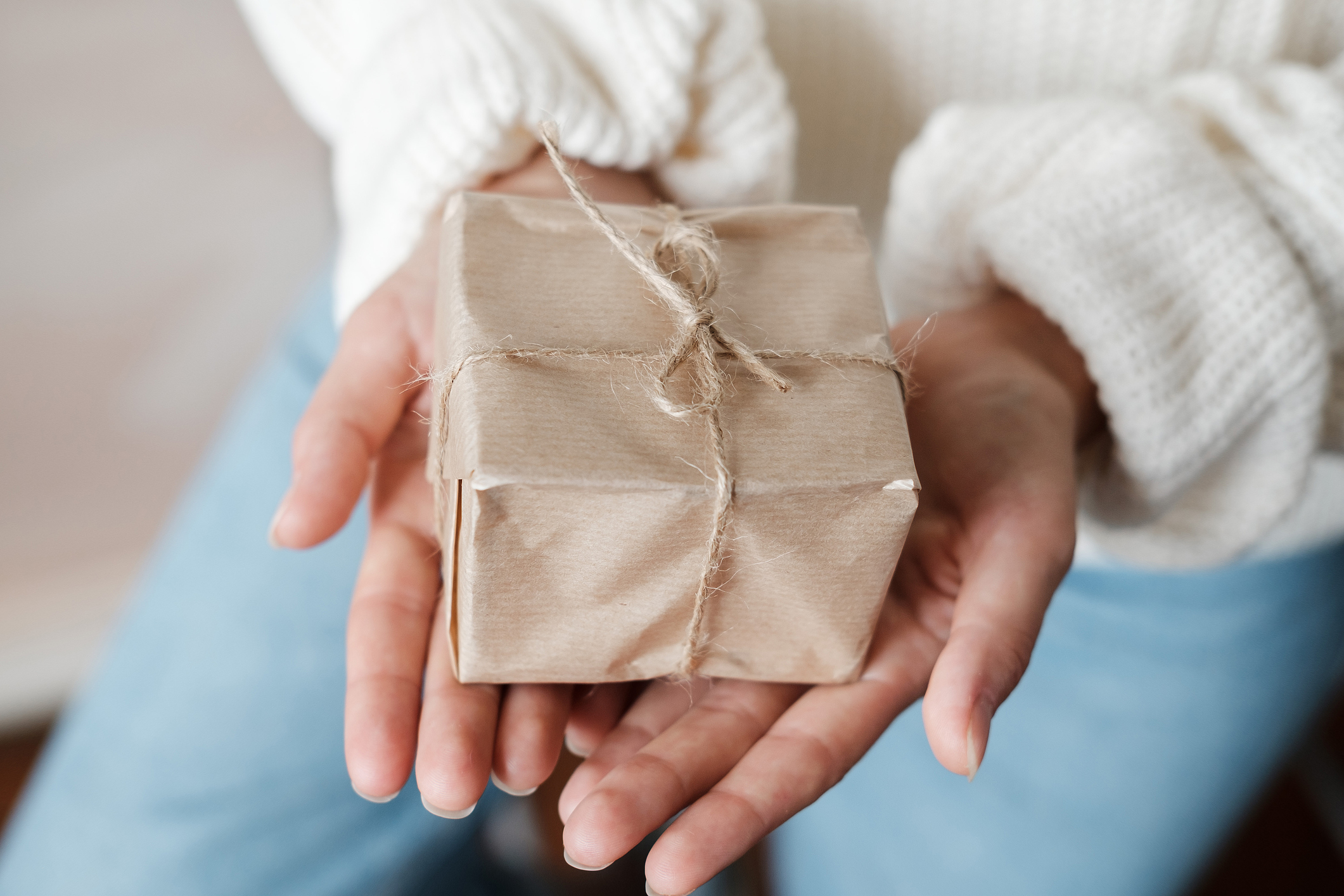 Hands offering out a gift wrapped in brown paper and twine.