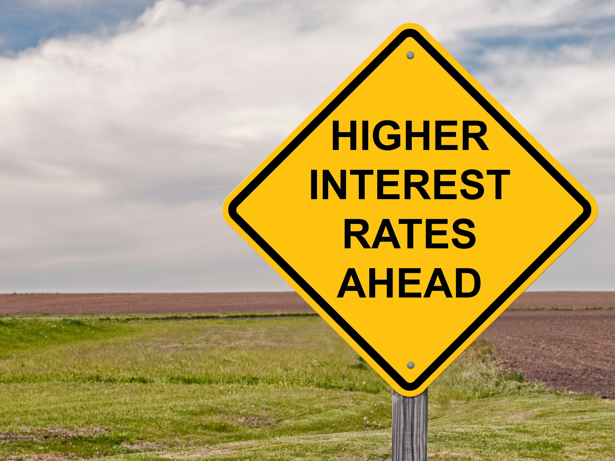 """road sign that reads """"higher interest rates ahead."""""""