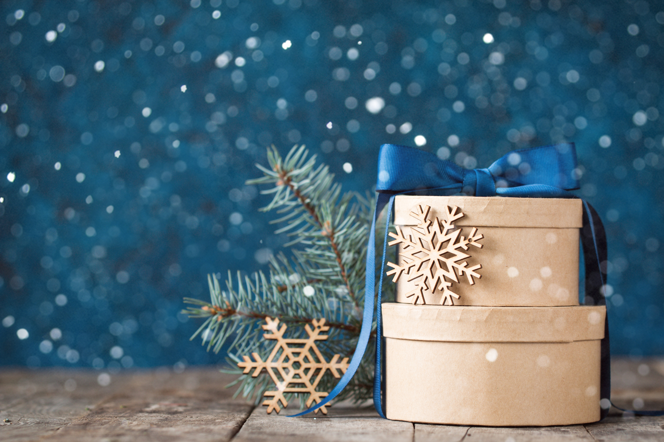 Wrapped gift boxes decorated with a blue bow, wooden snowflakes, and a pine branch.