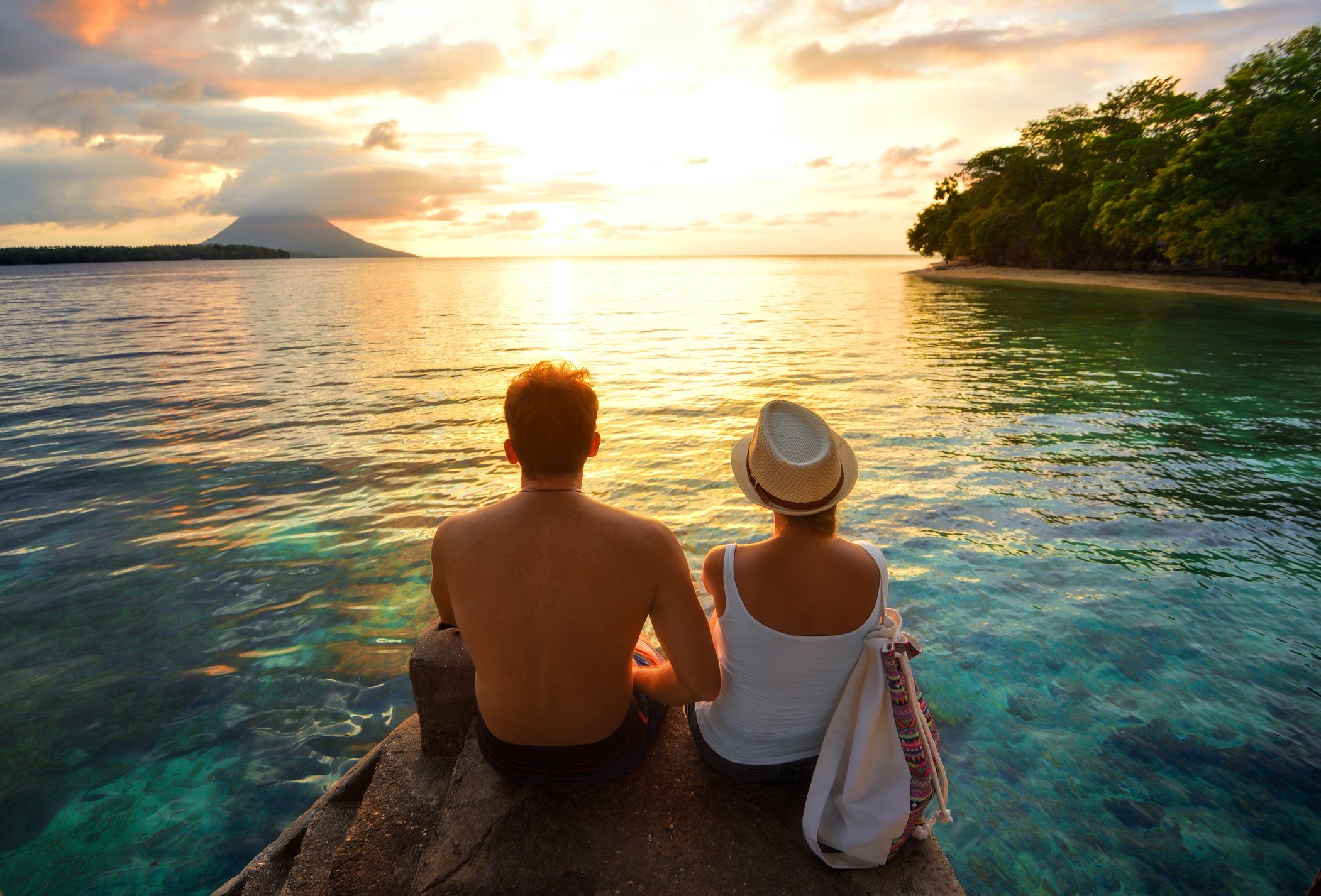 Couple sitting over the water watching a tropical sunset