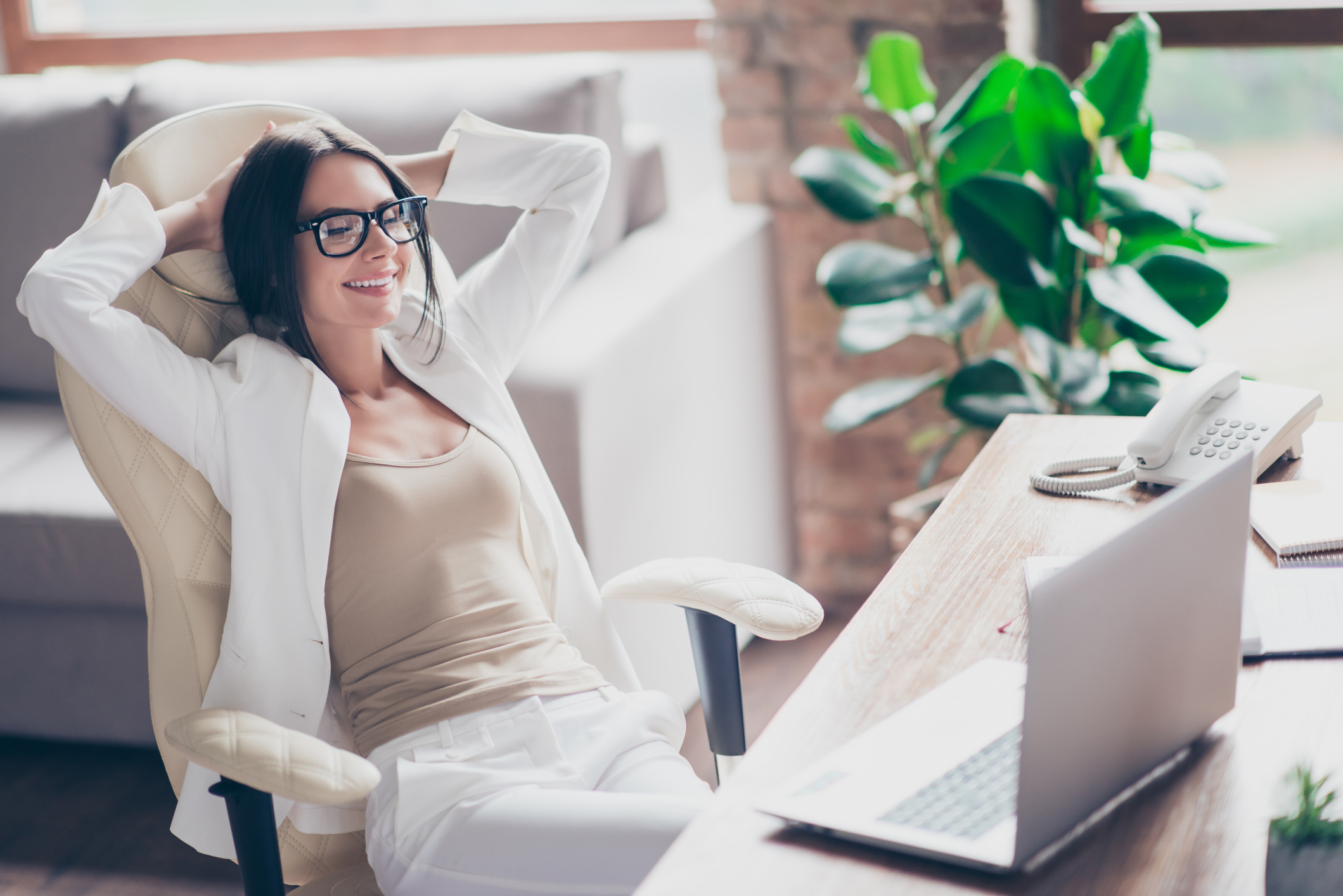 Content woman in glasses laying back in office chair with hands behind her head.