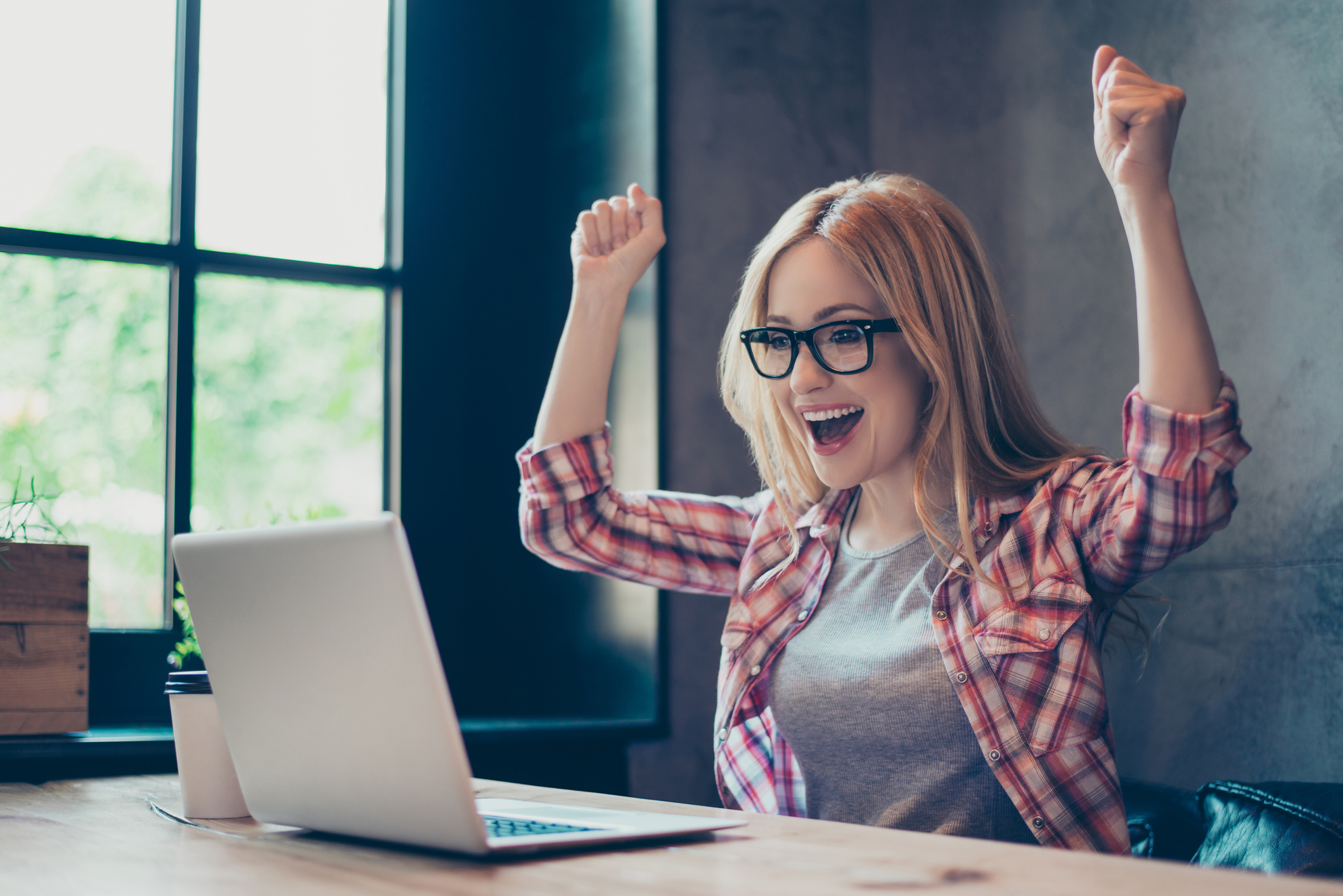 Excited Young Woman Raising Hands In The Air Looking At Her Laptop