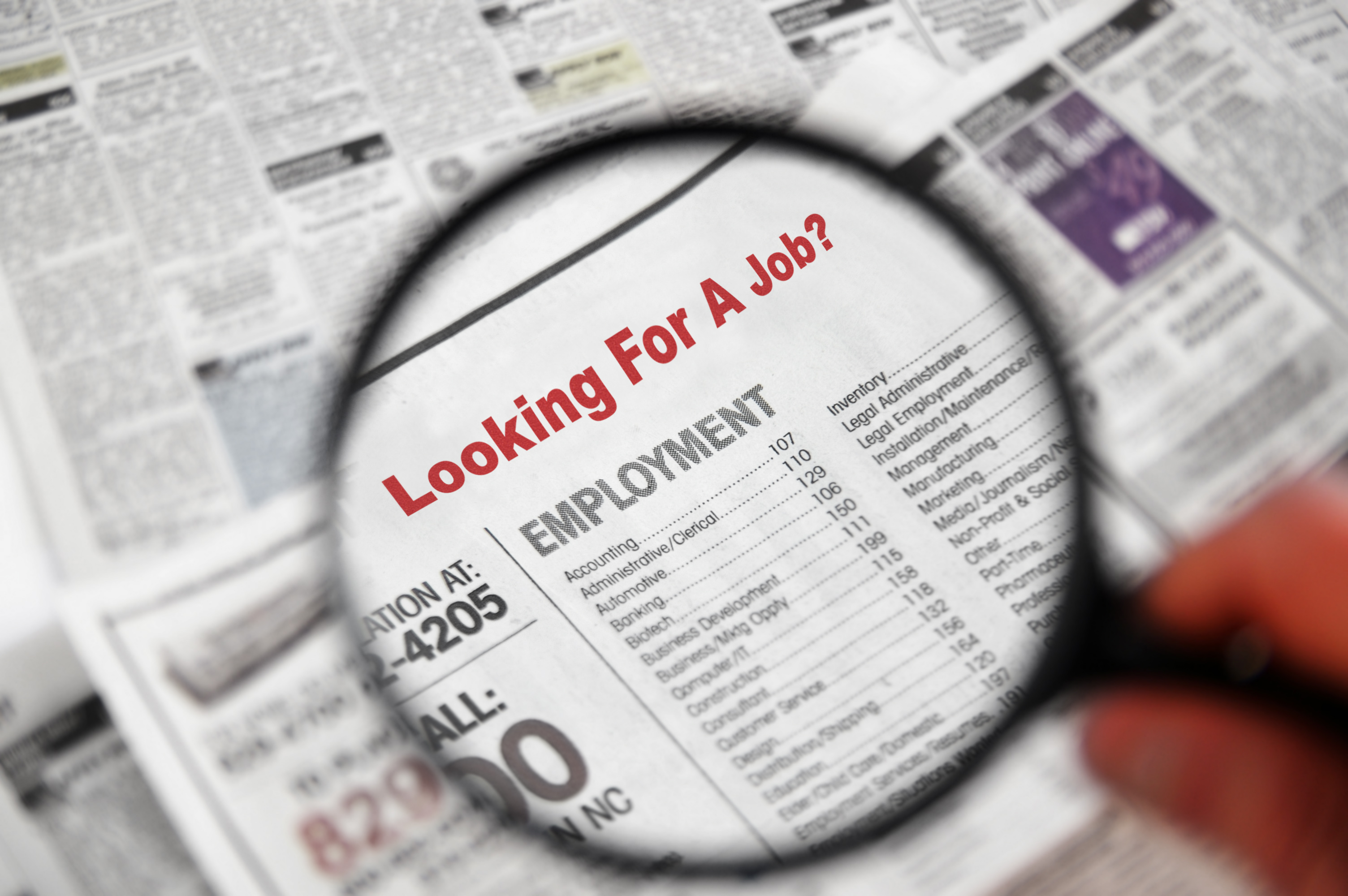 Magnifying glass looking at employment section of newspaper.