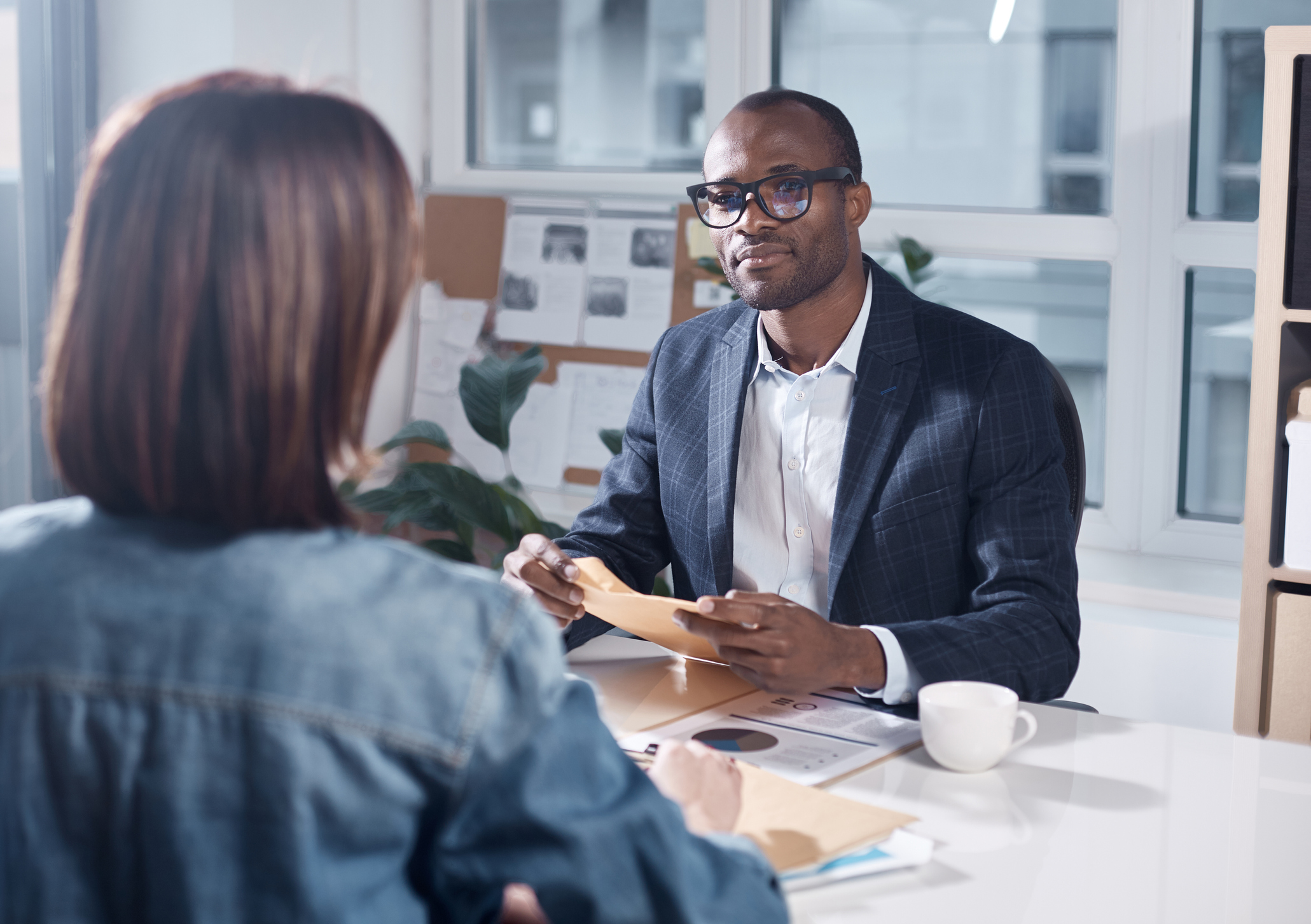 Man holding a folder while having a business meeting with a woman.