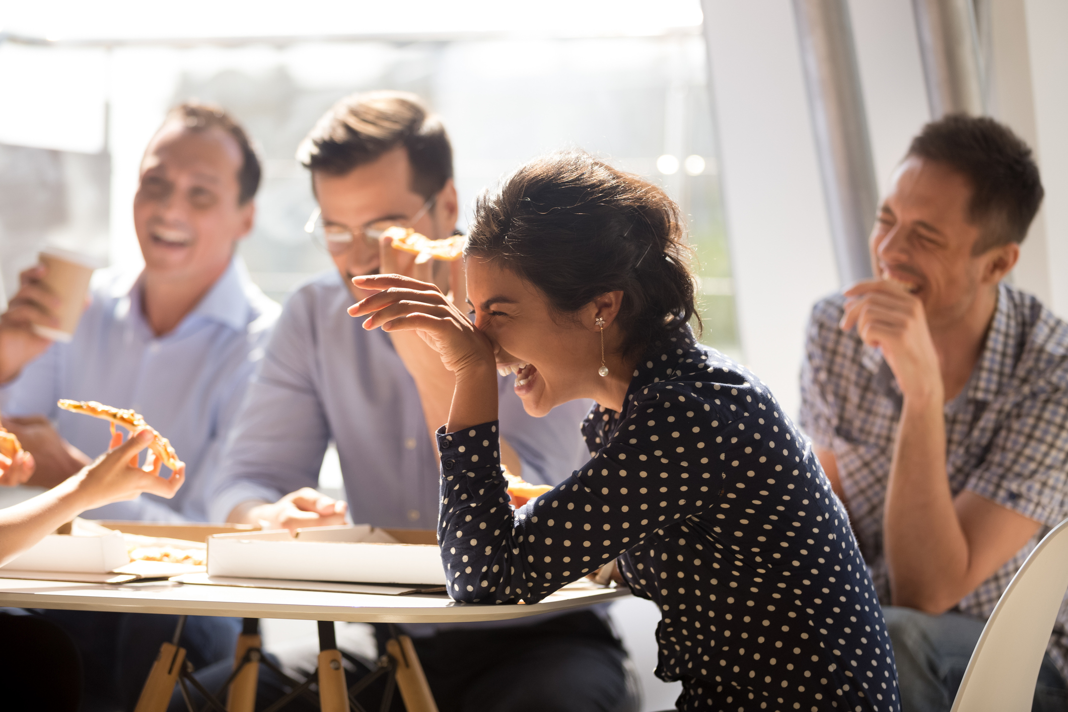 A group of office employees laughing and eating pizza.