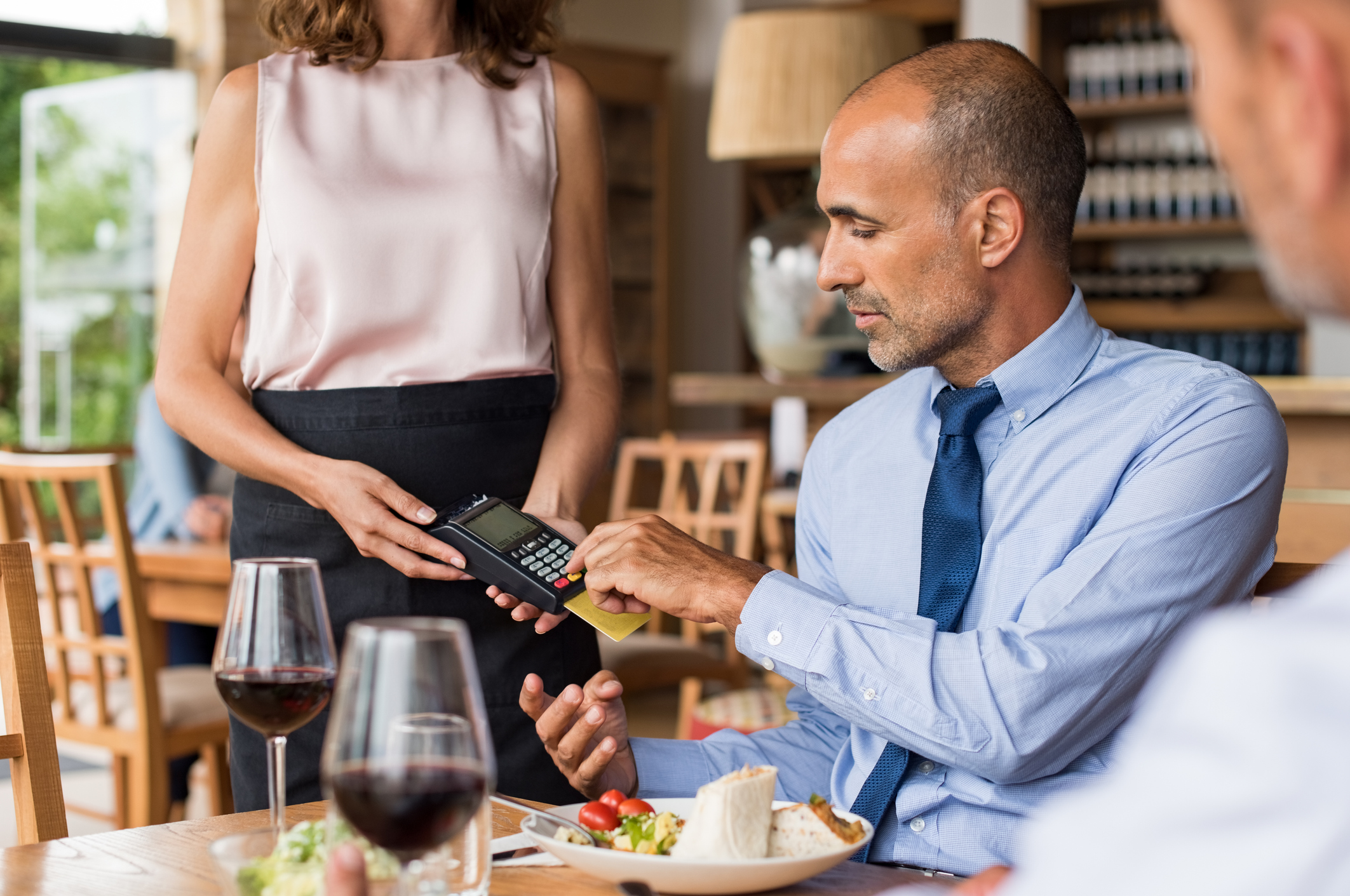 A businessman paying with a credit card at a restaurant.