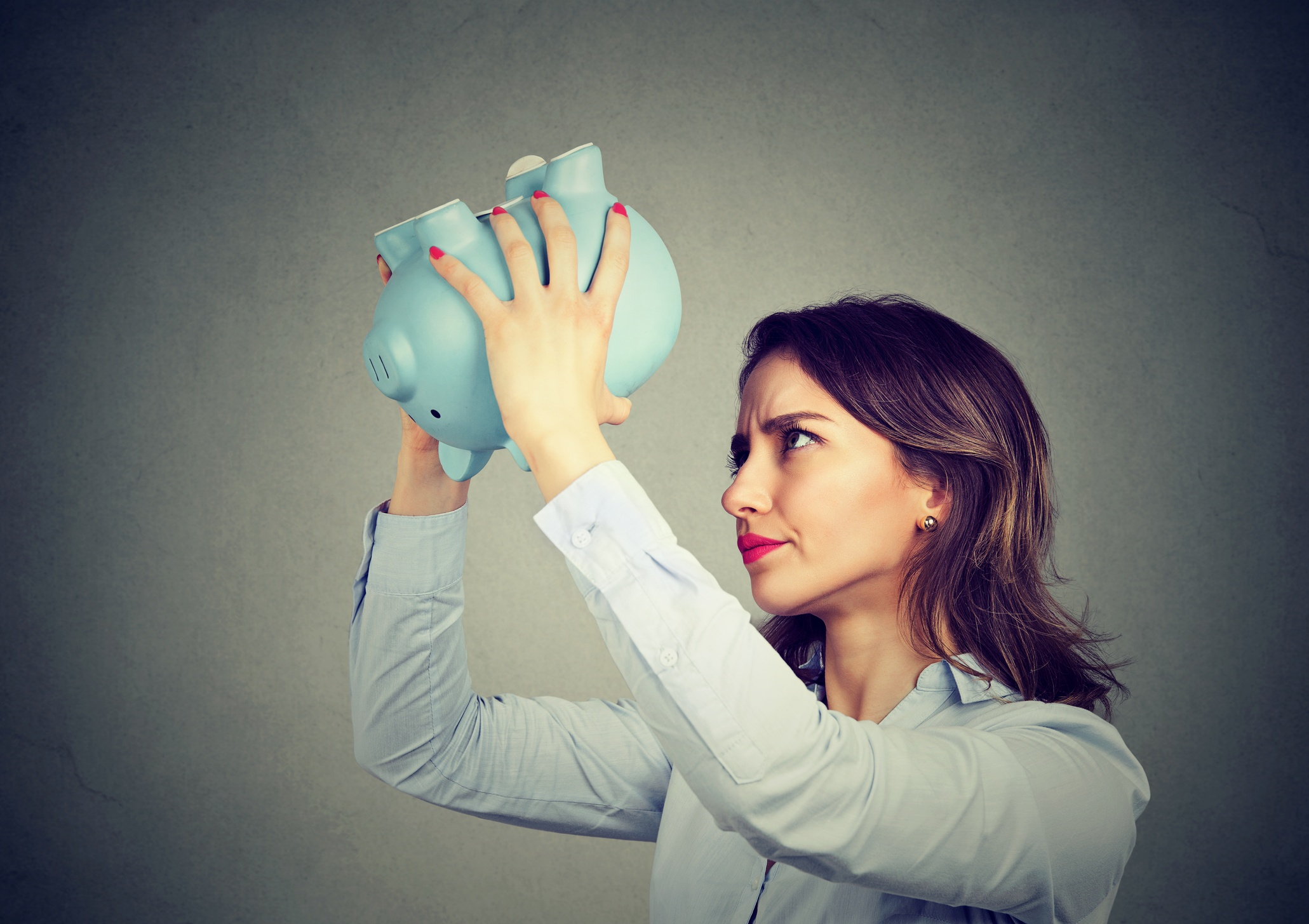 Young Woman Holding Empty Piggy Bank