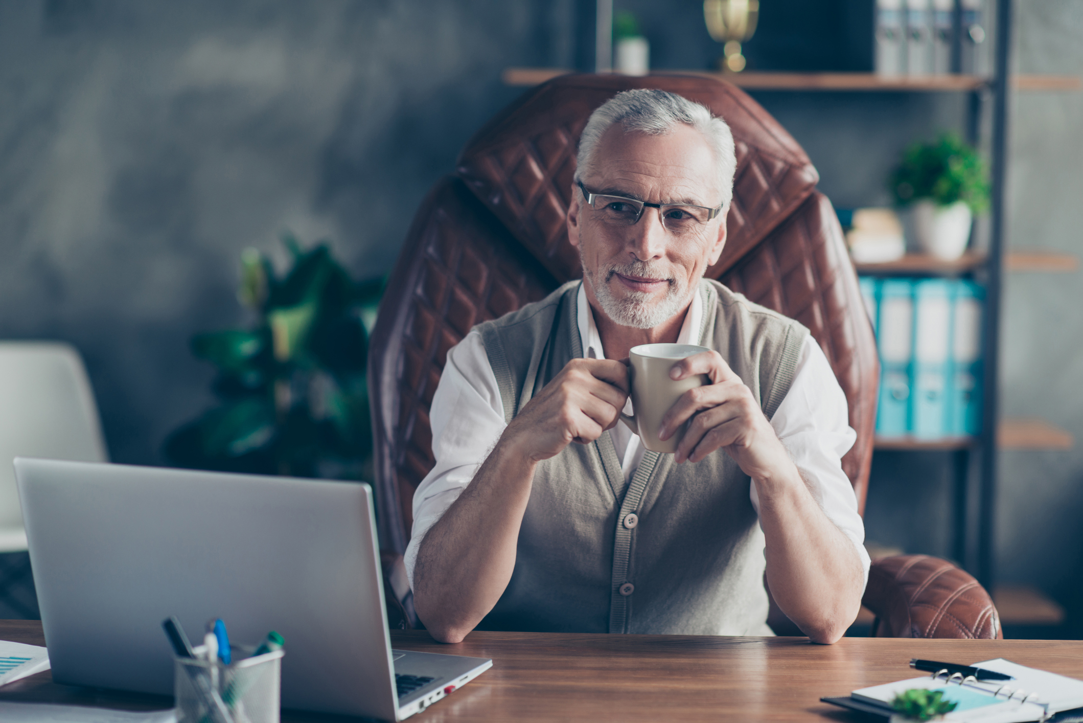 Rich older man sitting in a leather chair at his desk.