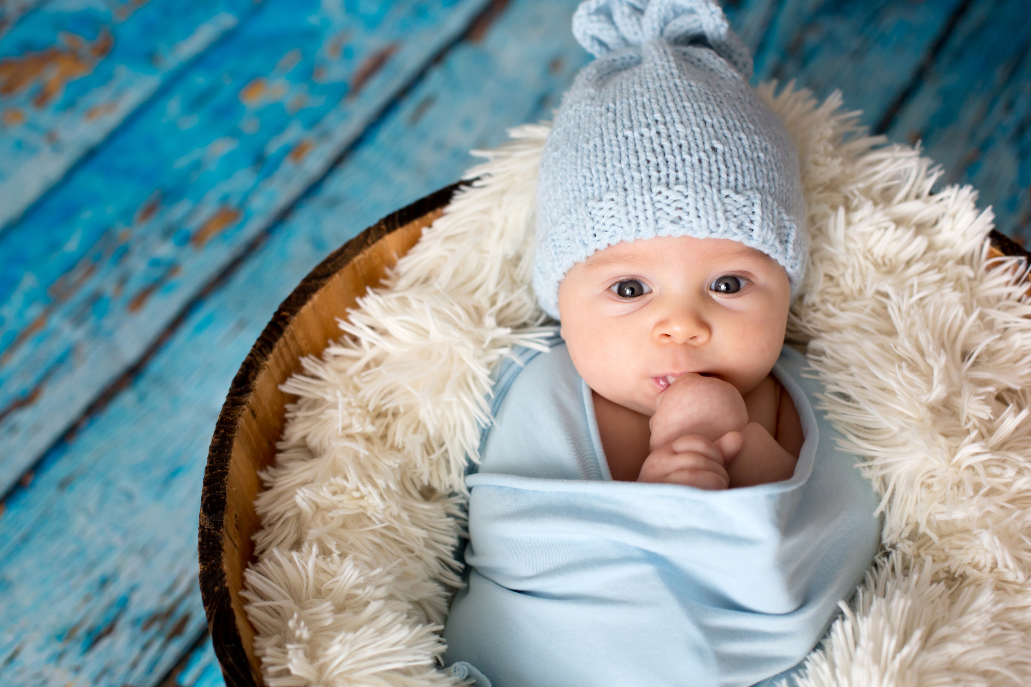 A baby swaddled in a blue blanket and hat.