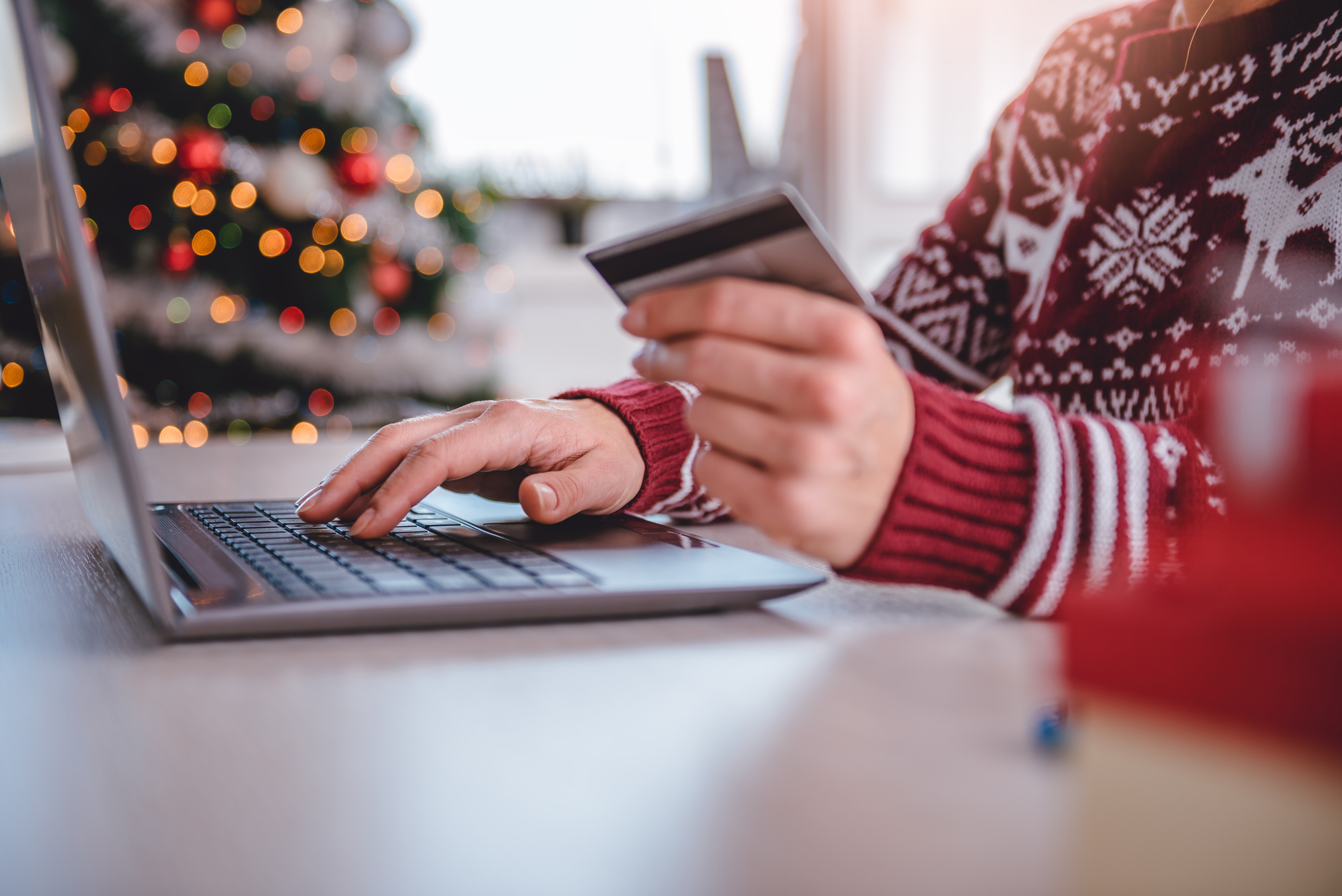 A person in a holiday sweater holding a credit card while typing on a laptop.