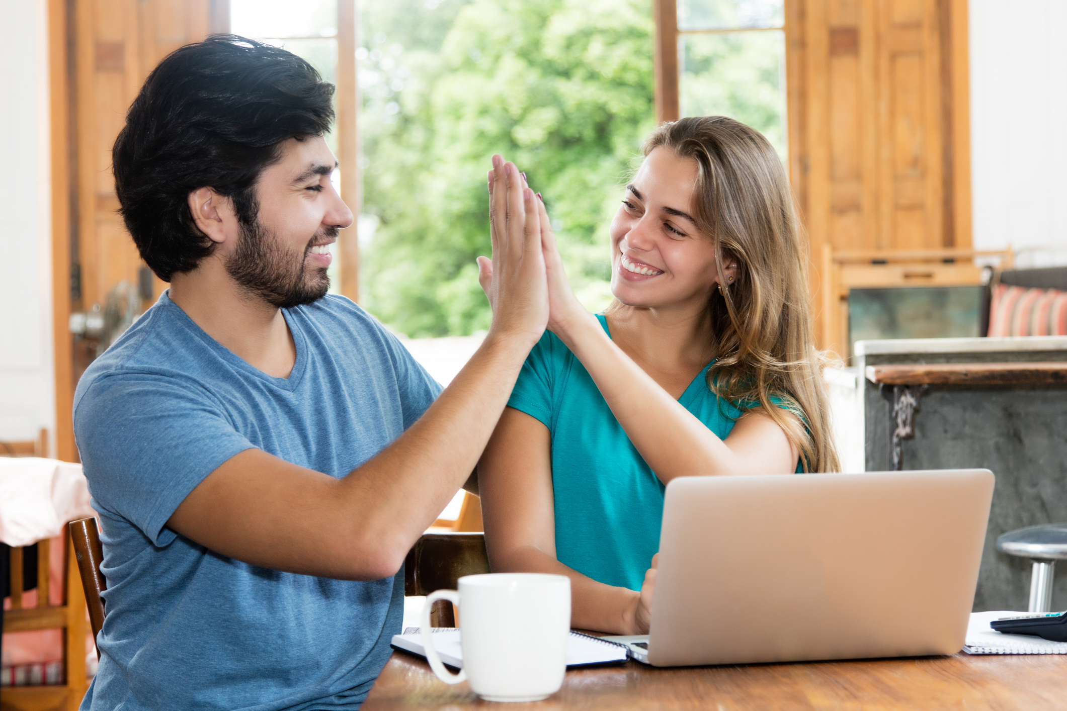 Young Couple High-Fiving In Front Of Laptop