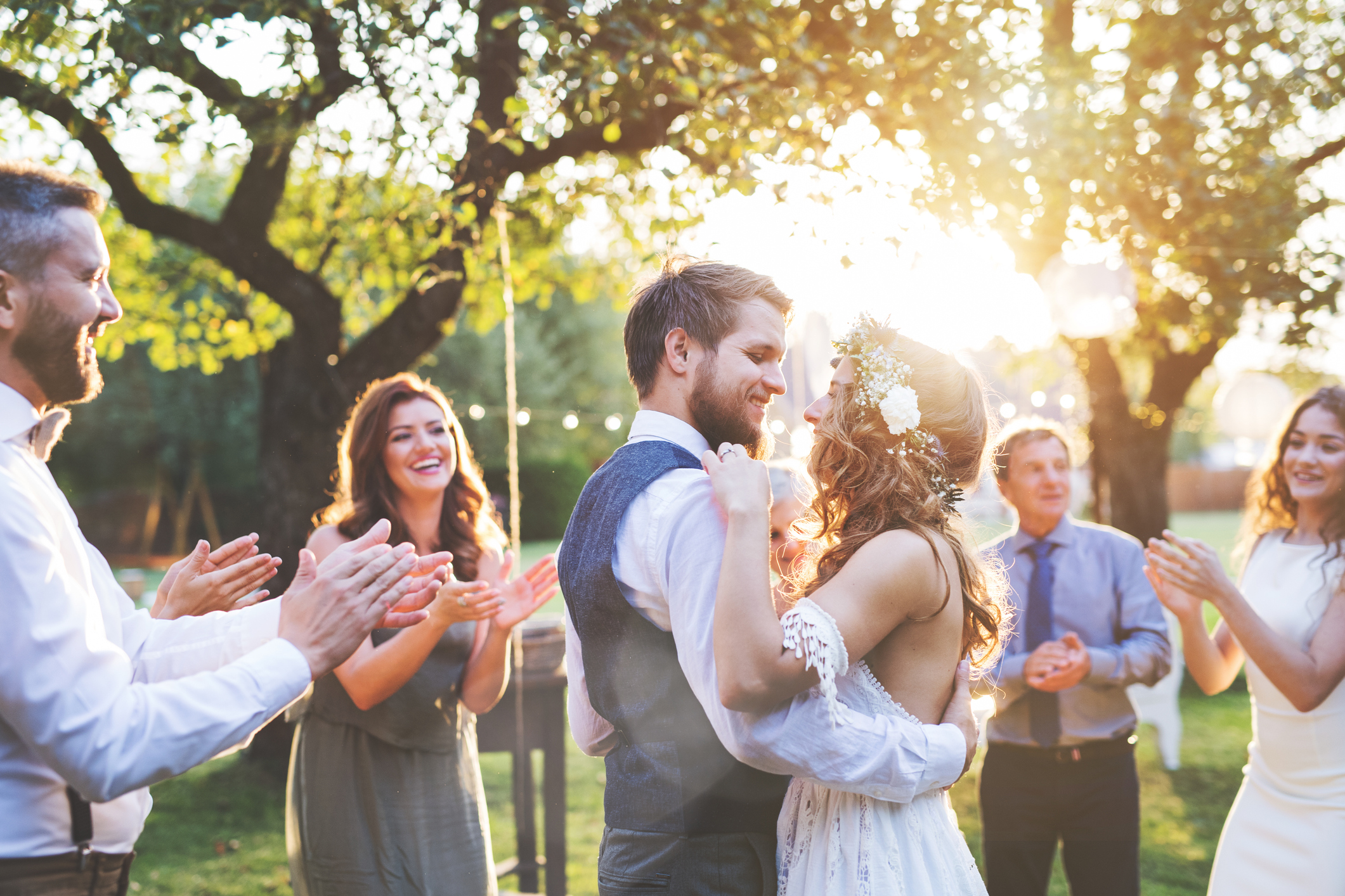 Happy Couple Embracing At Their Wedding While Surrounded By Friends And Family