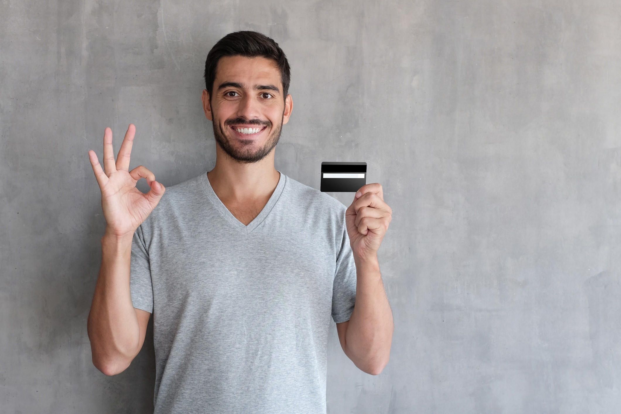 A smiling person holding a credit card.