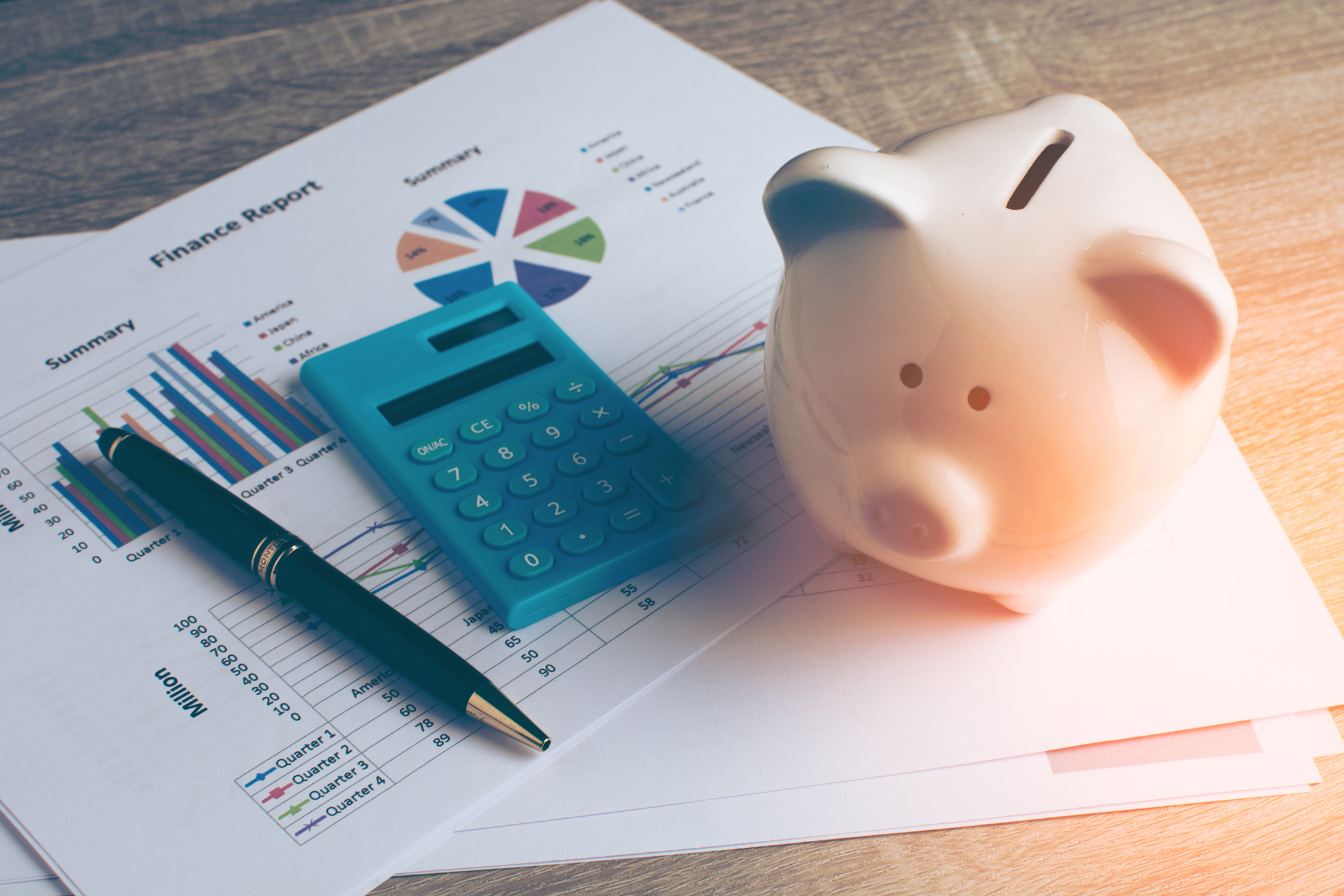 Financial report with a calculator, pen and piggy bank.