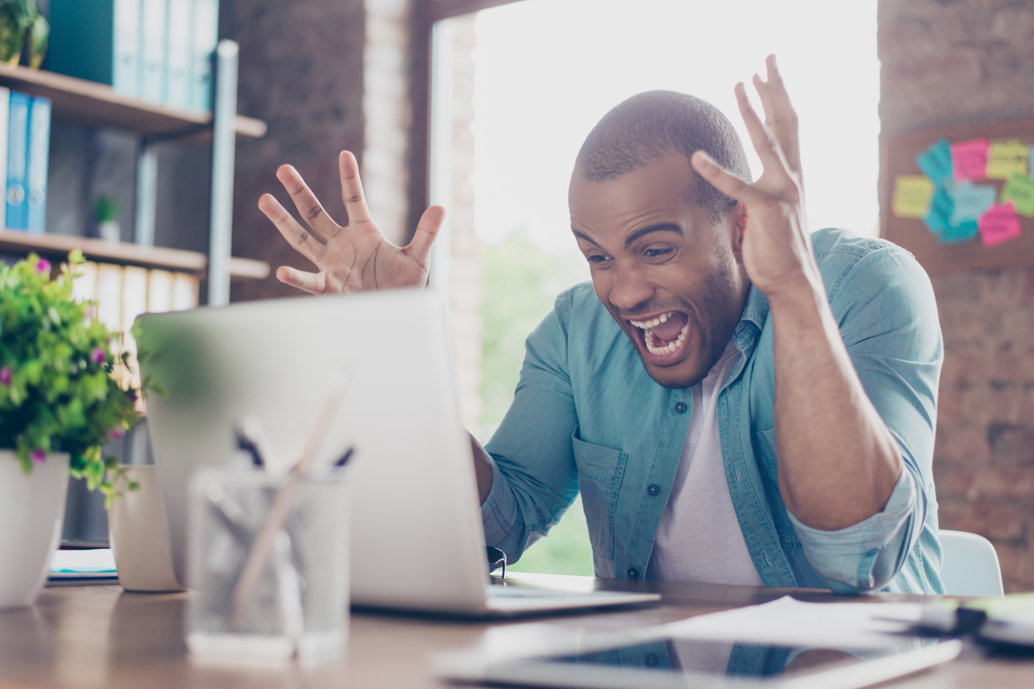 Man in shock yelling at laptop with hands in the air.