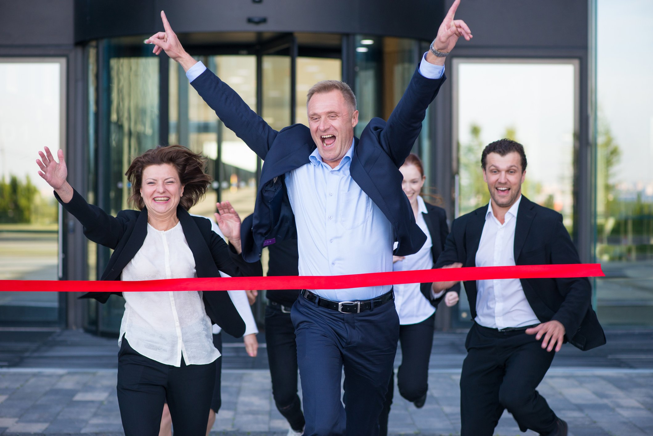 Business people triumphantly running through red ribbon.
