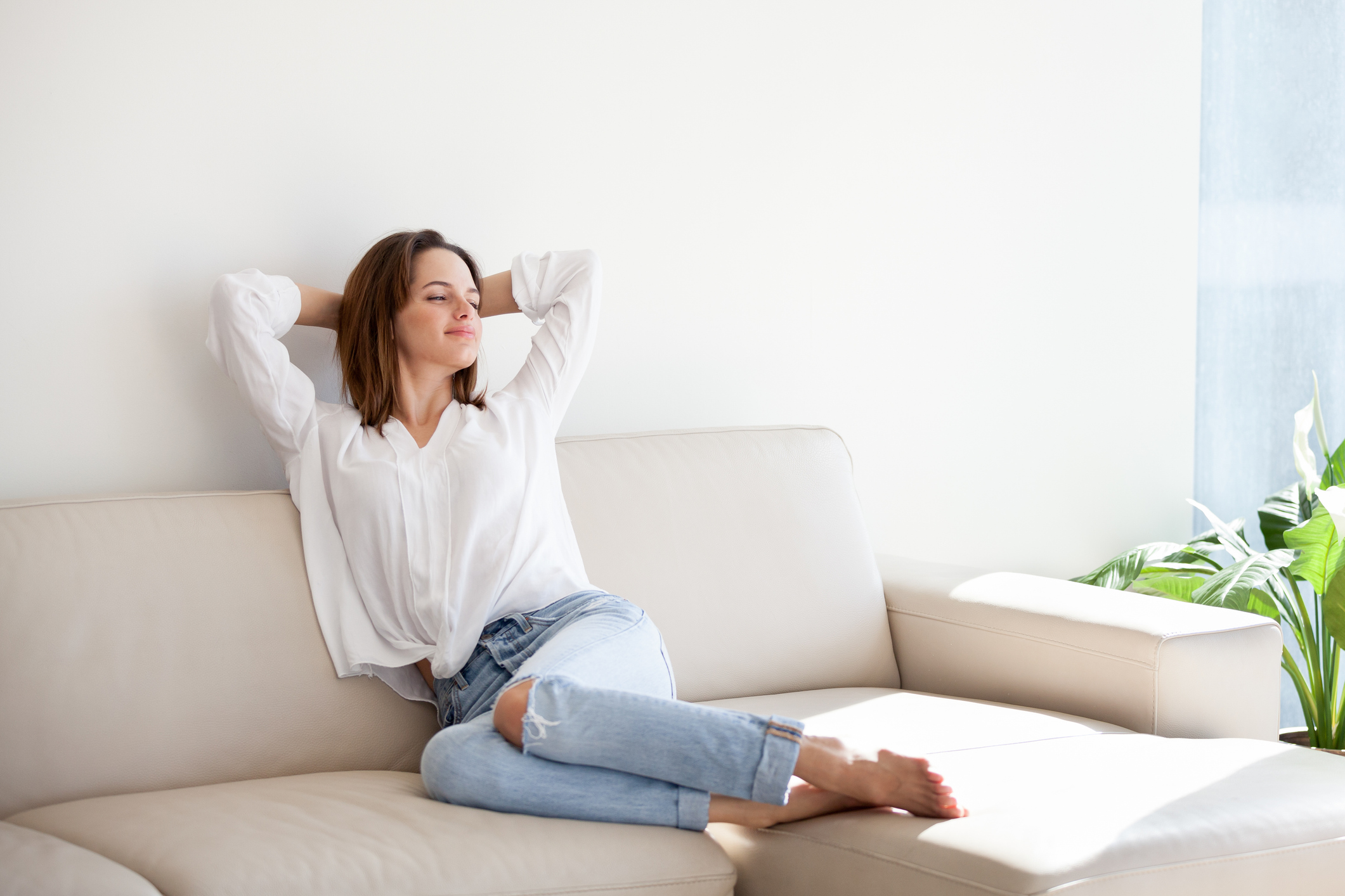 A relaxed woman sitting on her couch with her hands behind her head.