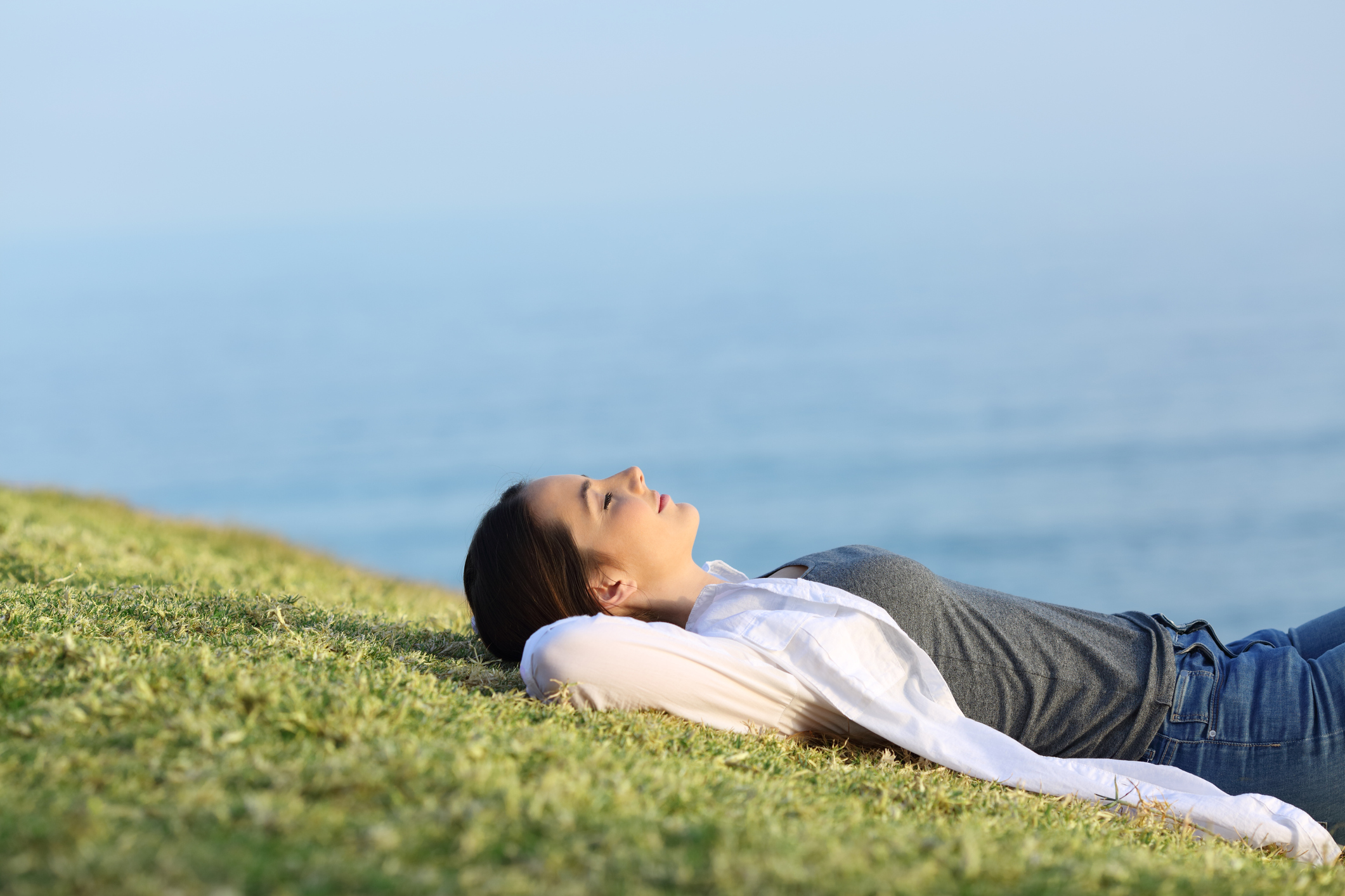 Relaxed woman lying on a grassy hill overlooking the ocean.