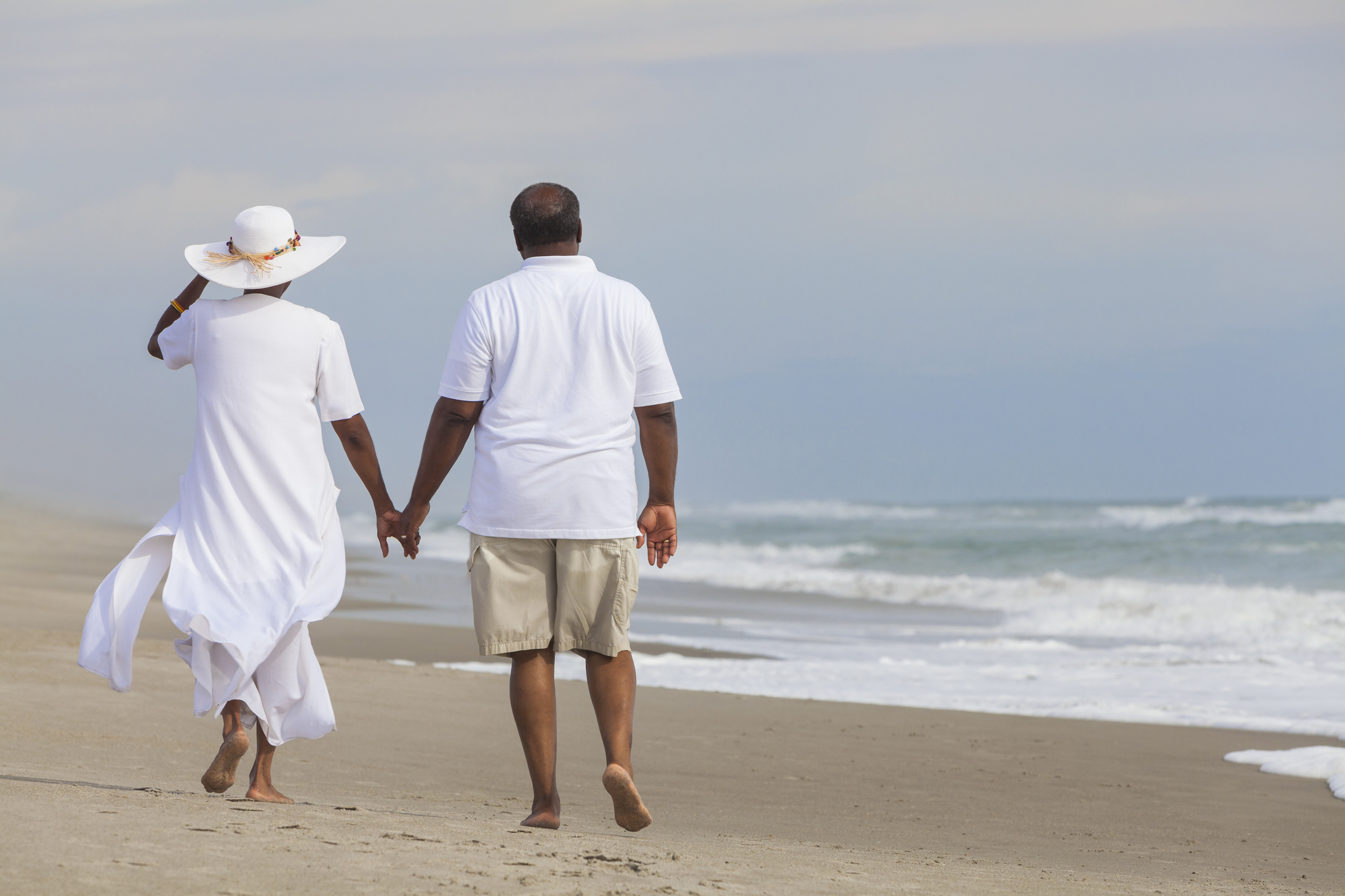 An older couple holds hands while walking across the beach.