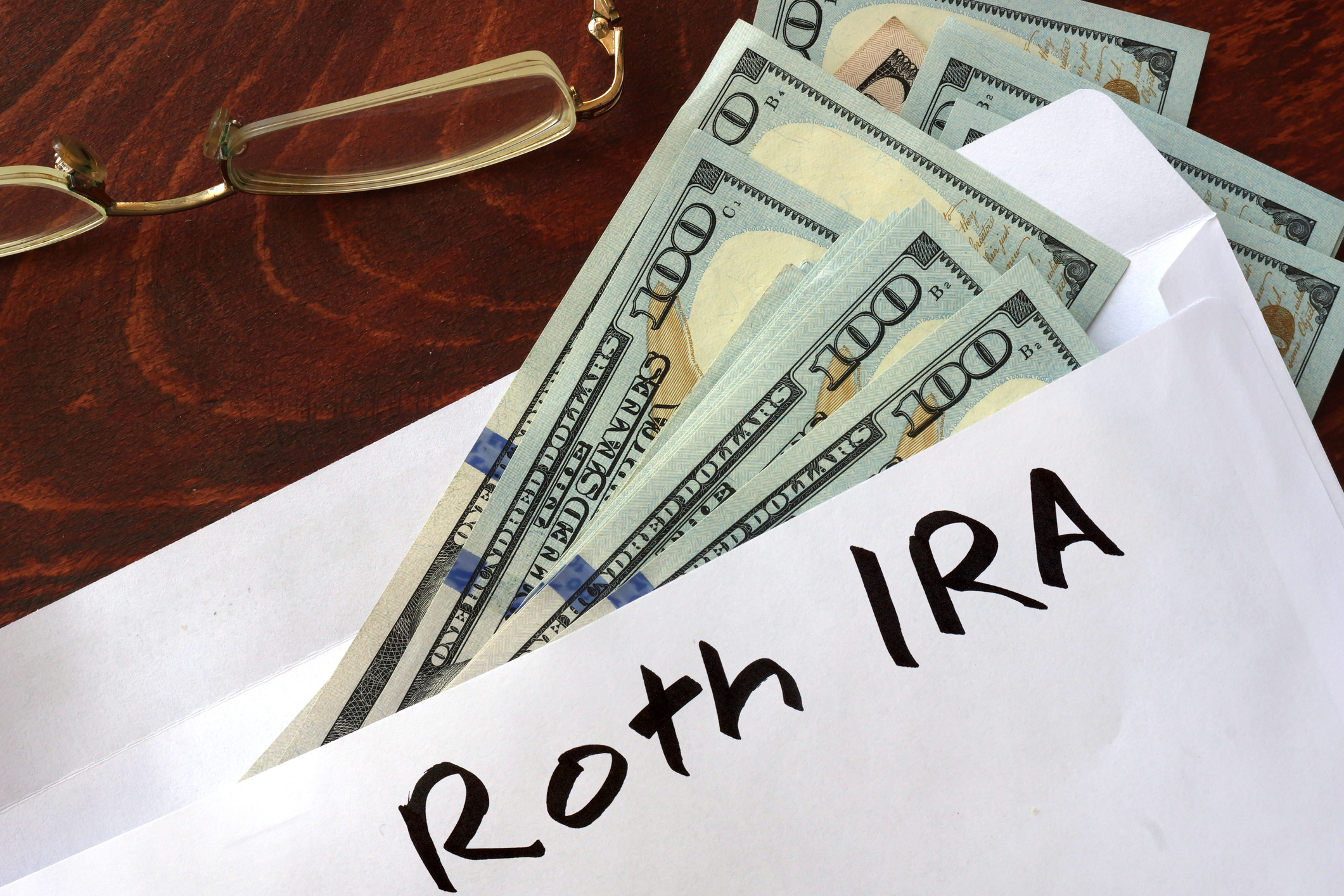 An envelope with Roth IRA written on it and $100 bills falling out.