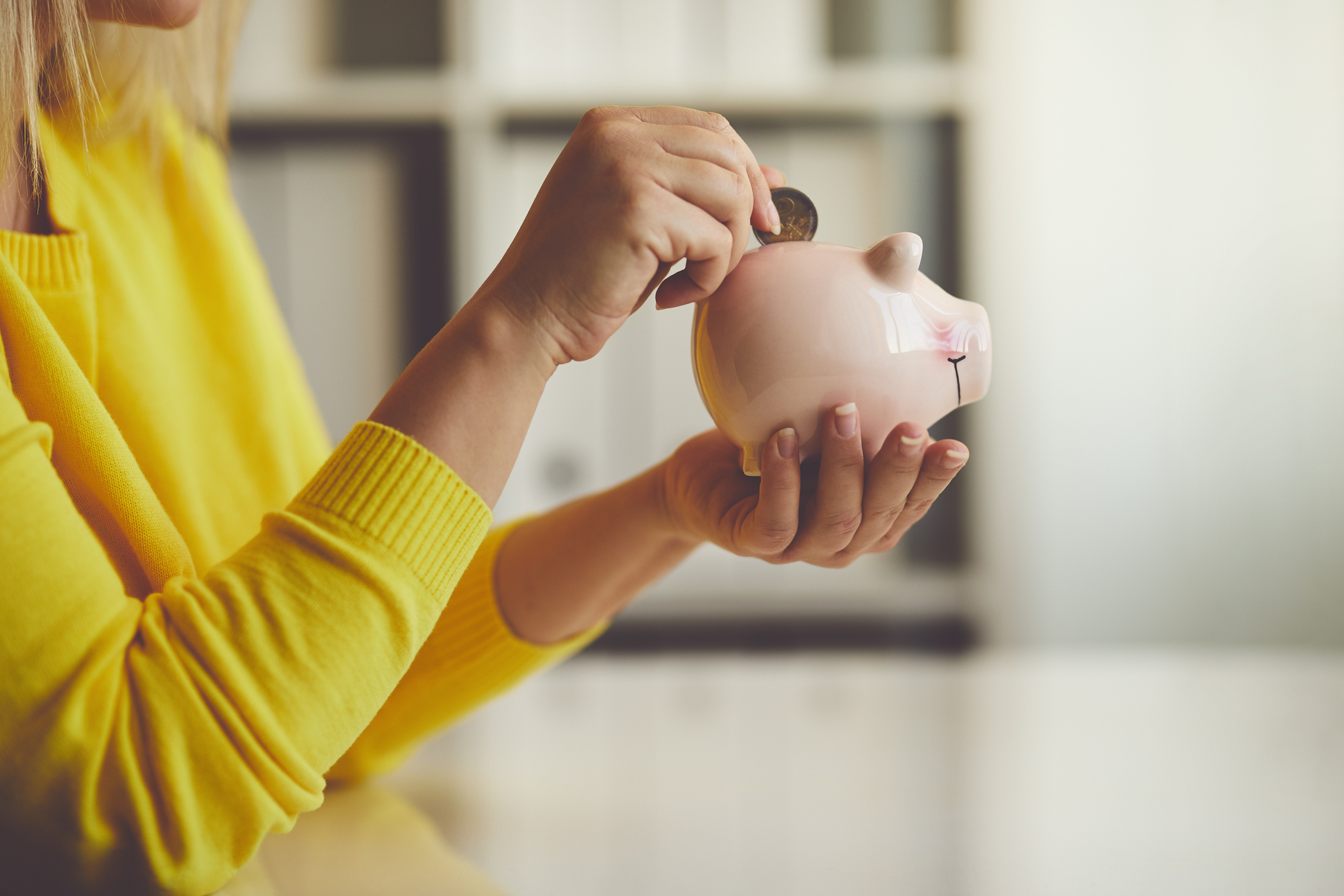 Woman putting coin in piggy bank.