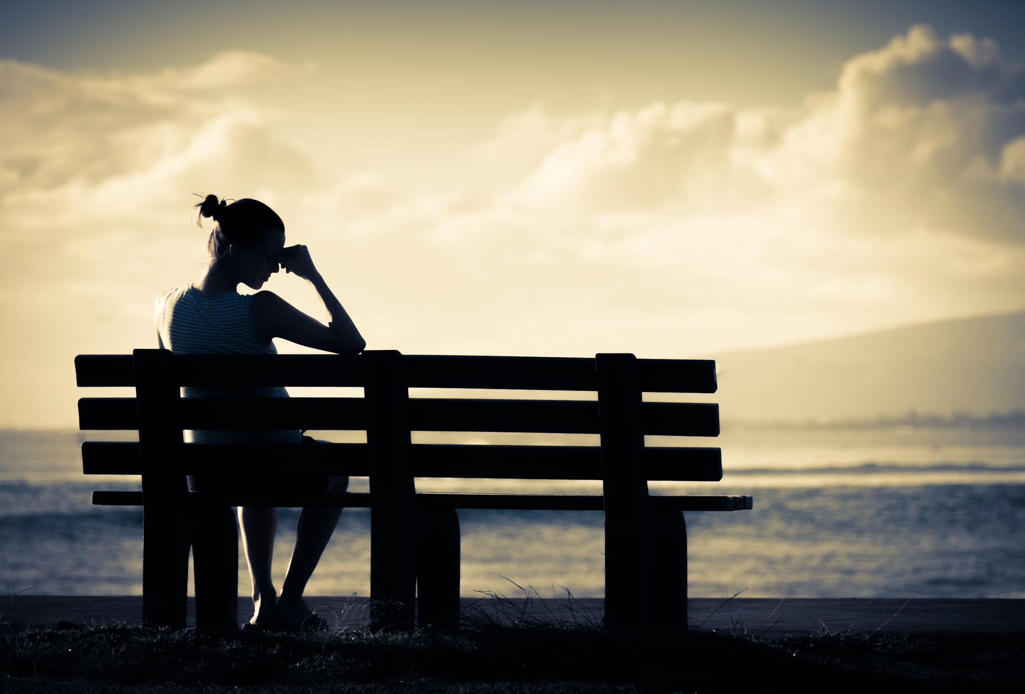 Silhouette of an upset woman on a waterfront bench.