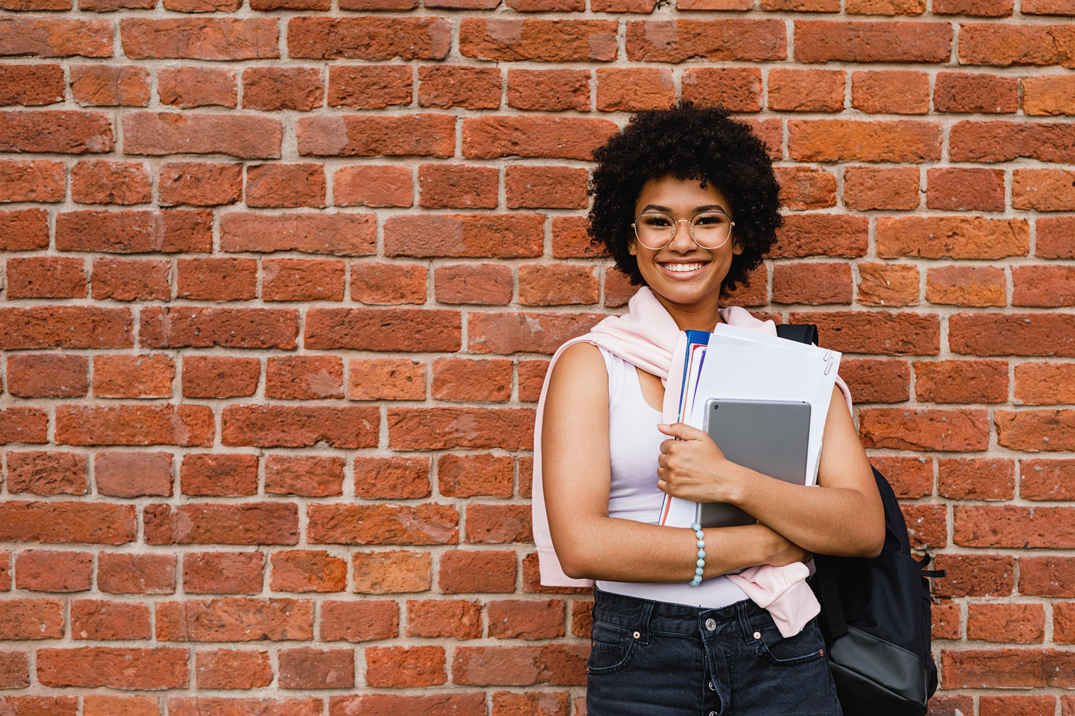 Smiling woman with books and tablet standing against brick wall.