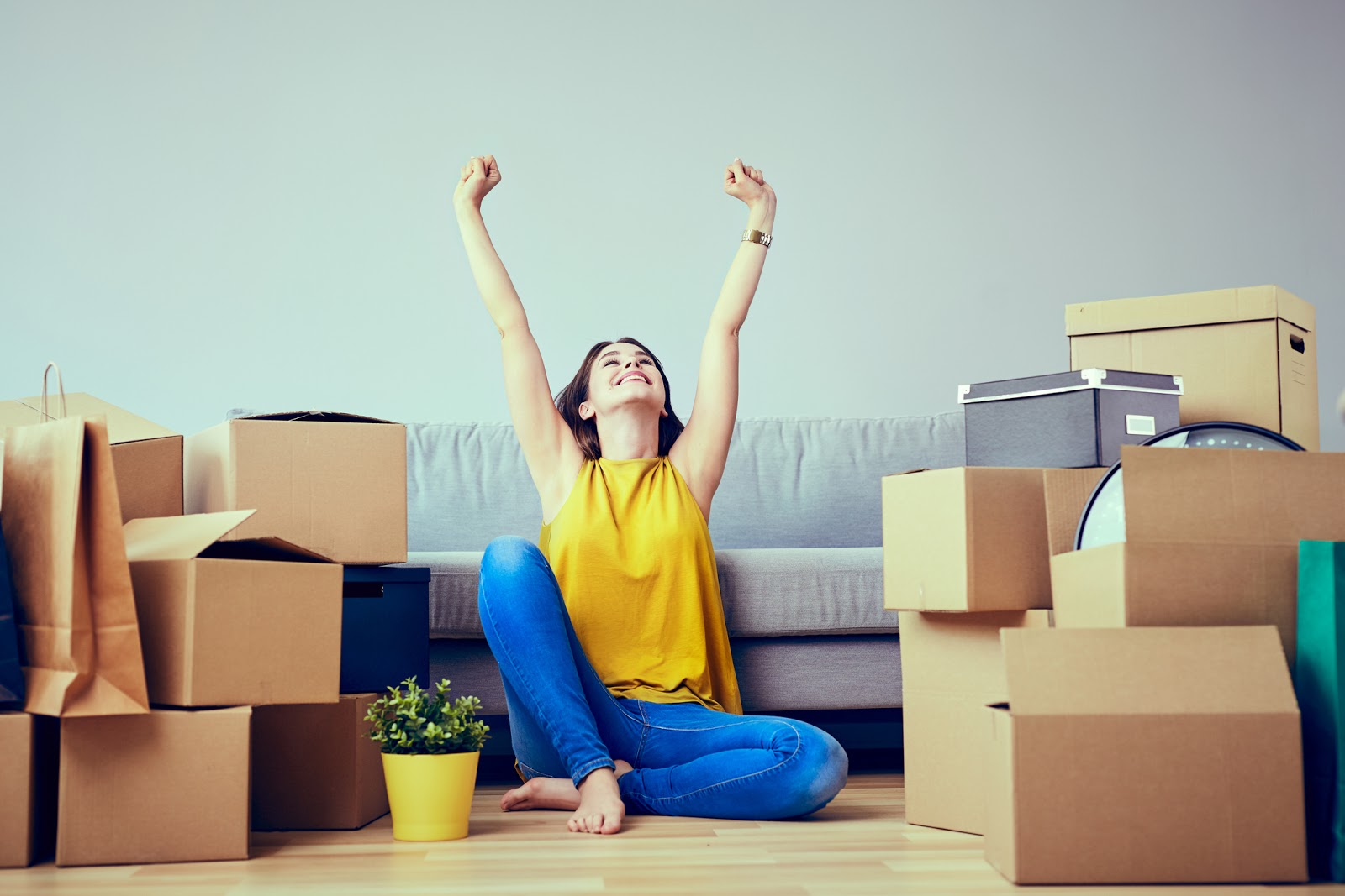 Happy Young Woman Sitting In New Home Between Stacks Of Boxes