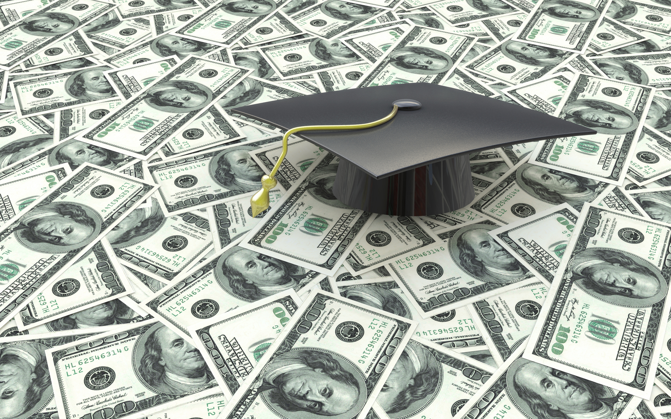 Graduation cap on top of a pile of money