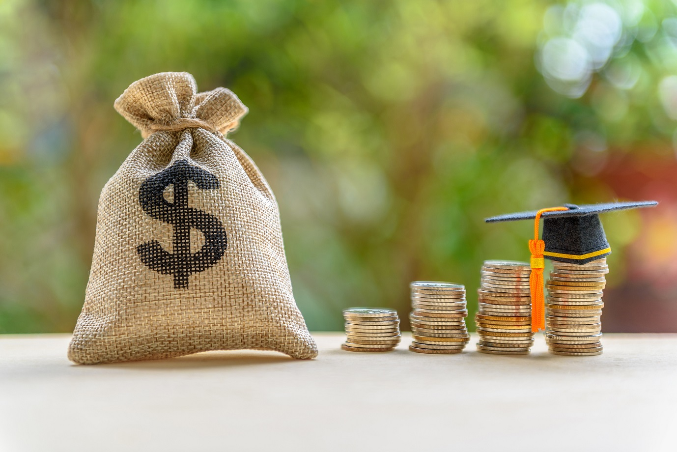 A bag with a dollar sign on it sits next to stacks of coins with a graduation cap at the top.