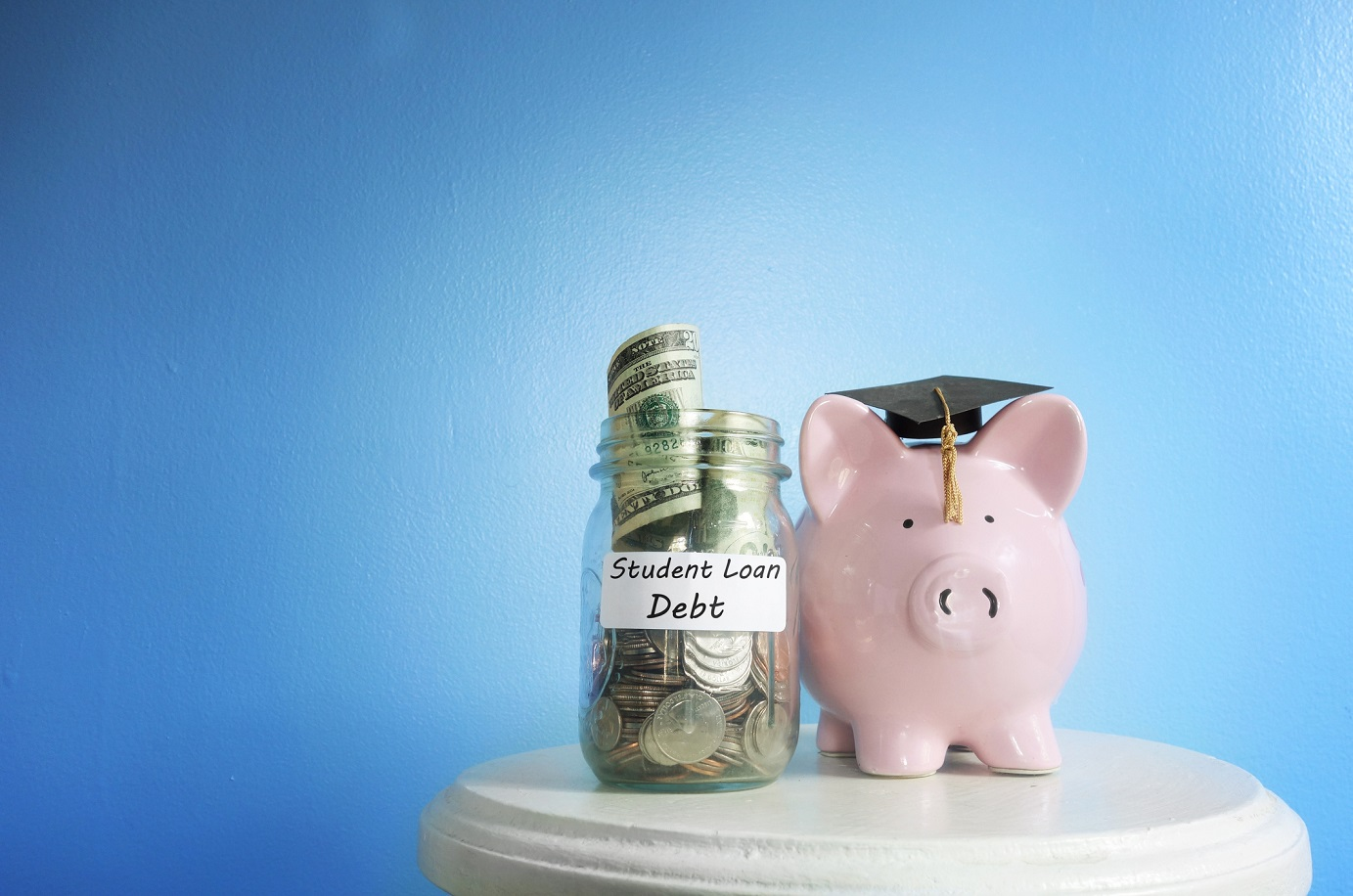 "A jar full of money labelled ""Student Loan Debt"" stands next to a piggy bank and graduation cap."