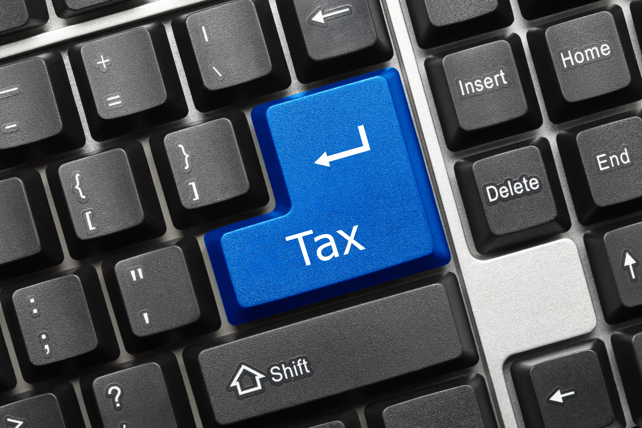 "A blue key on a black keyboard is labelled ""Tax""."
