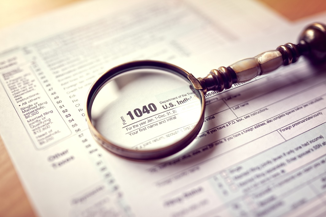 A magnifying glass lies over a tax form.