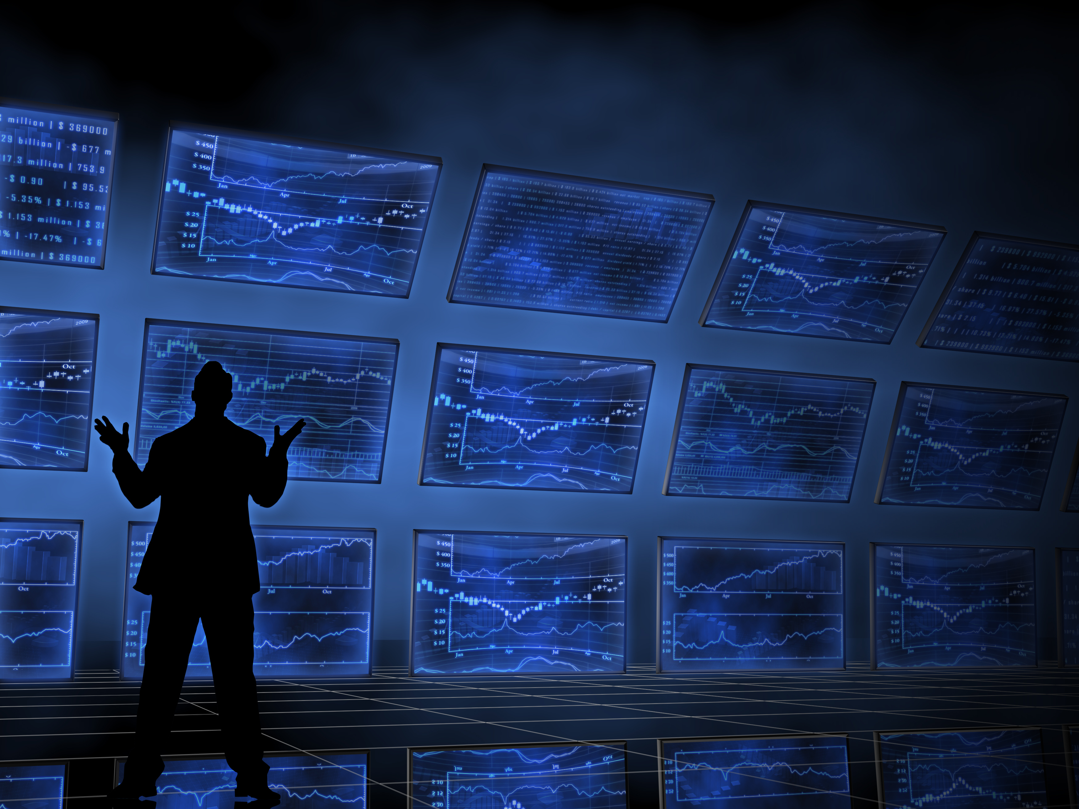 A person stands looking at rows of screens across a wall.