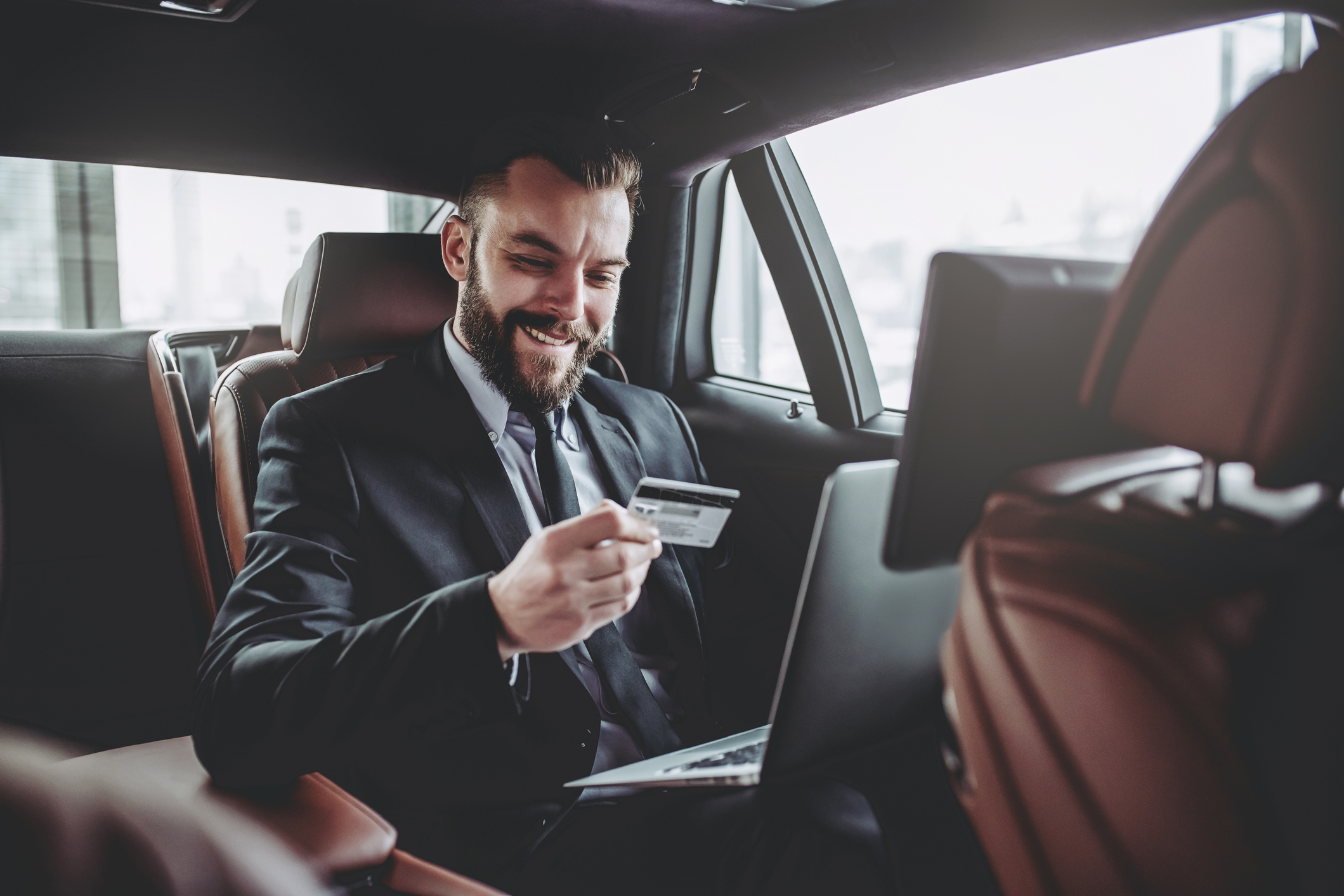 Man in suit in the back of a luxury car with laptop in his lap holding a credit card.