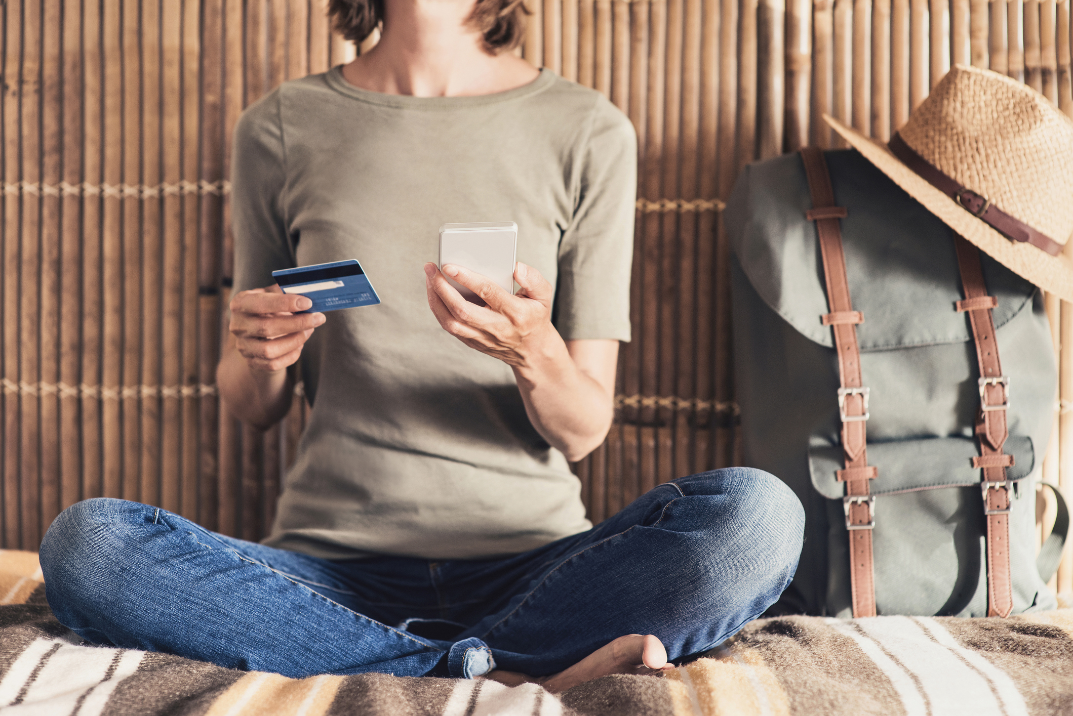 A woman sitting on the floor next to a backpack holding a phone and a credit card.