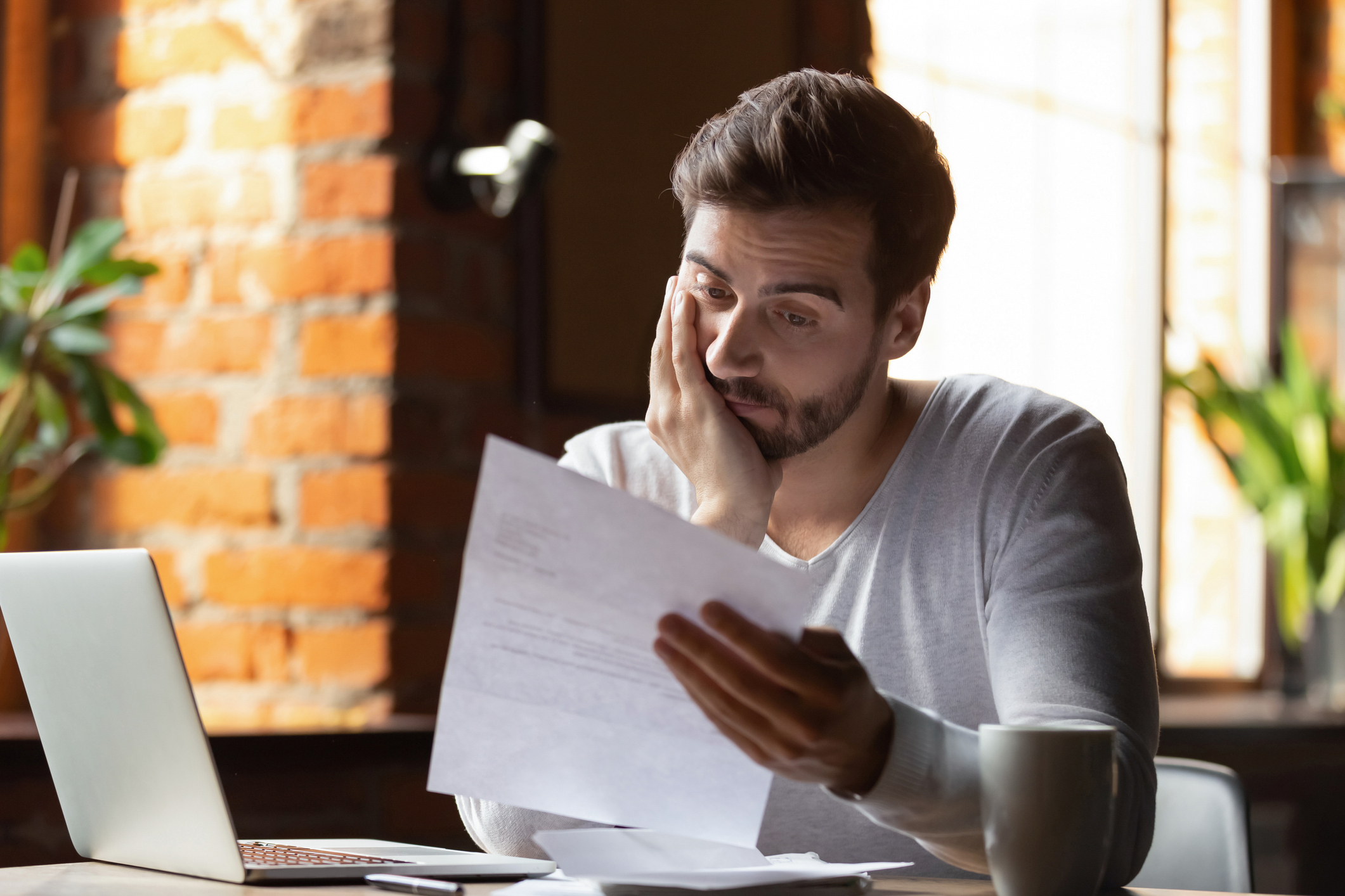 A man looking distressed while reading his credit card bill.