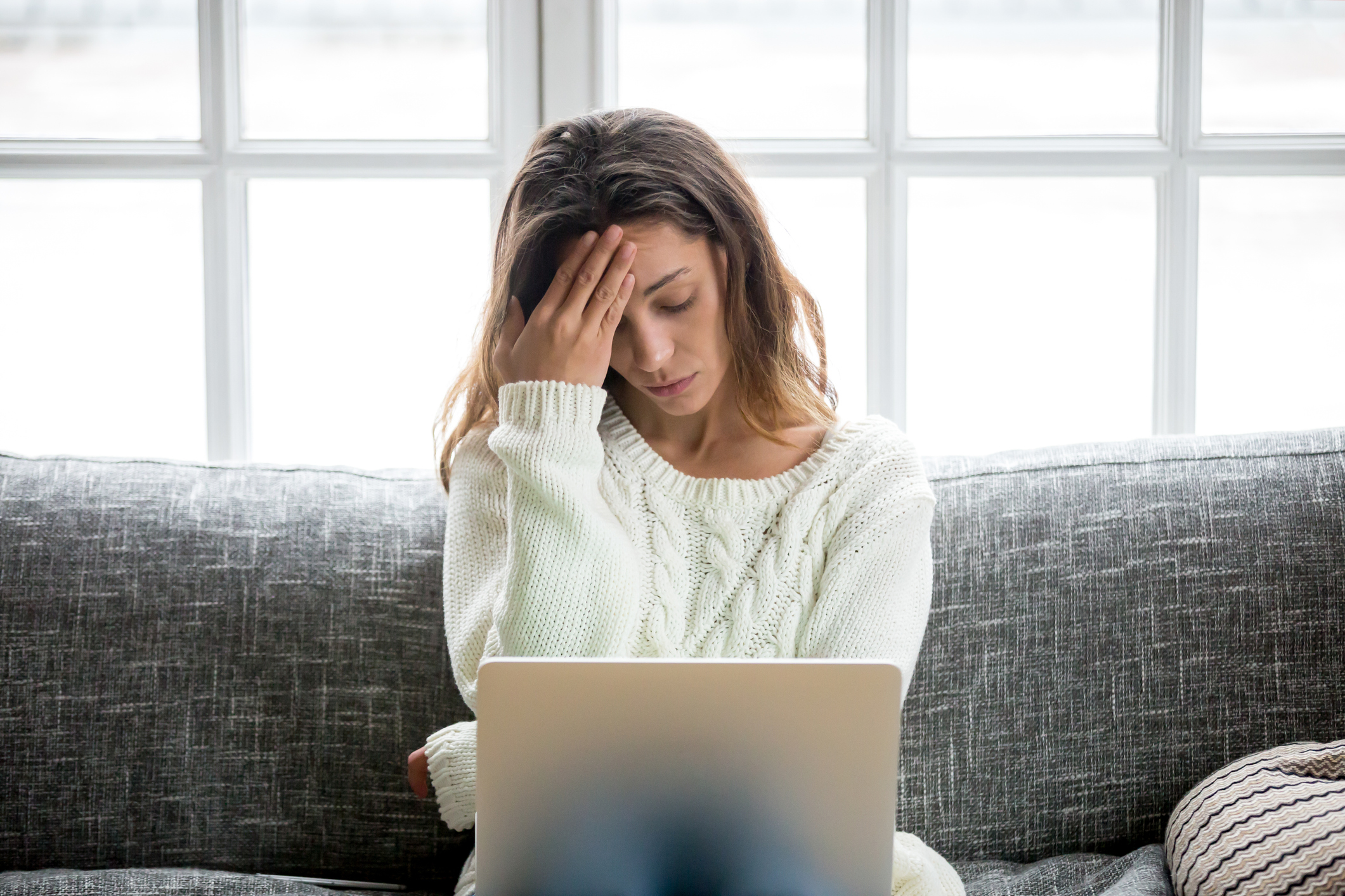 An upset woman on a couch staring at a laptop.