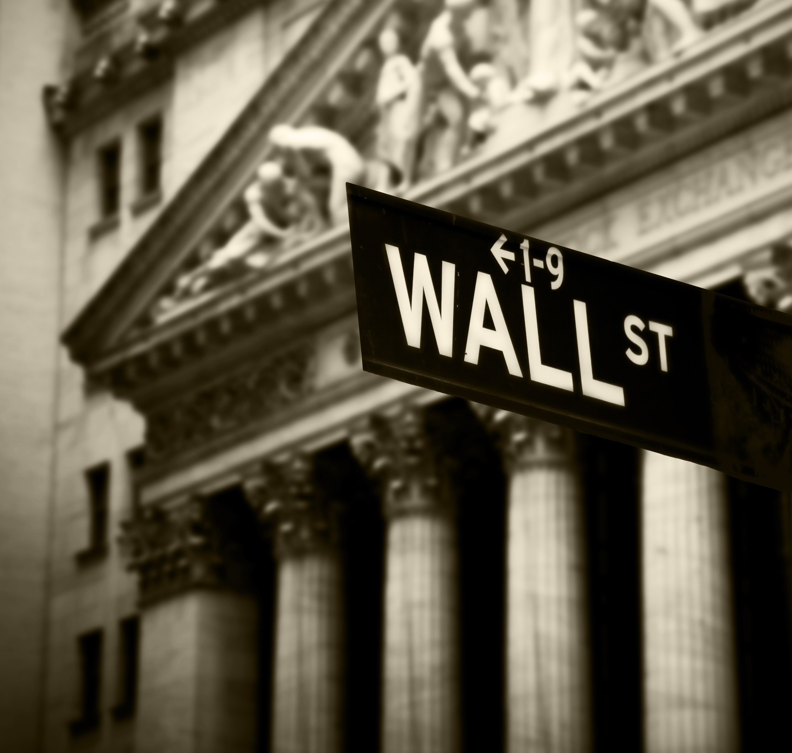 A Wall Street sign stands in front of a large building.