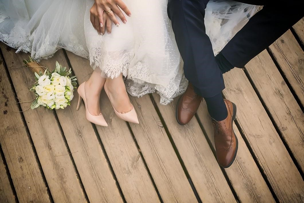 Wedding couple holding hands sitting on wooden deck beside bouquet.