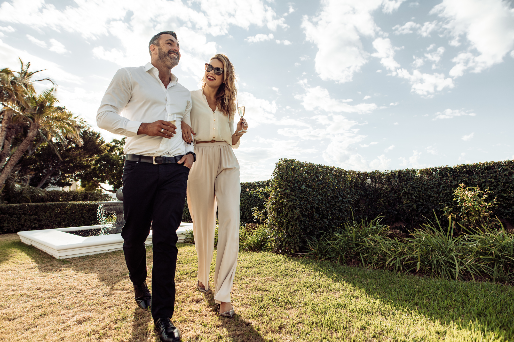 Well-dressed couple walking through greenery drinking champagne.