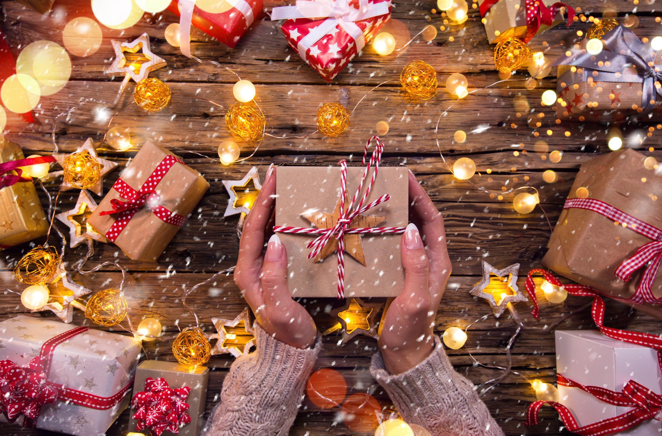 A woman's hands holding a wrapped gift over a table of lights and presents.