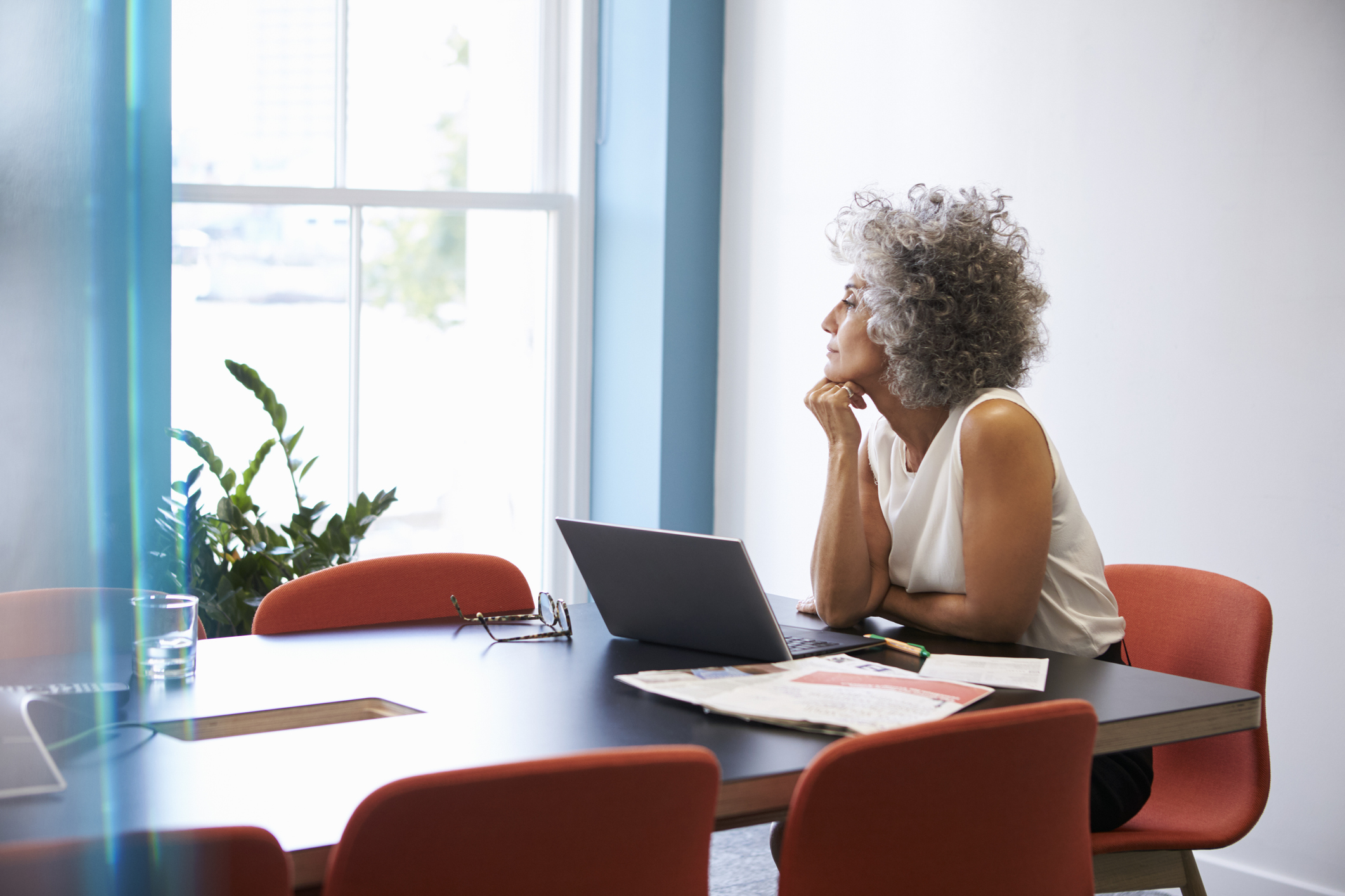 A middle-age woman sitting in an office looking thoughtful.