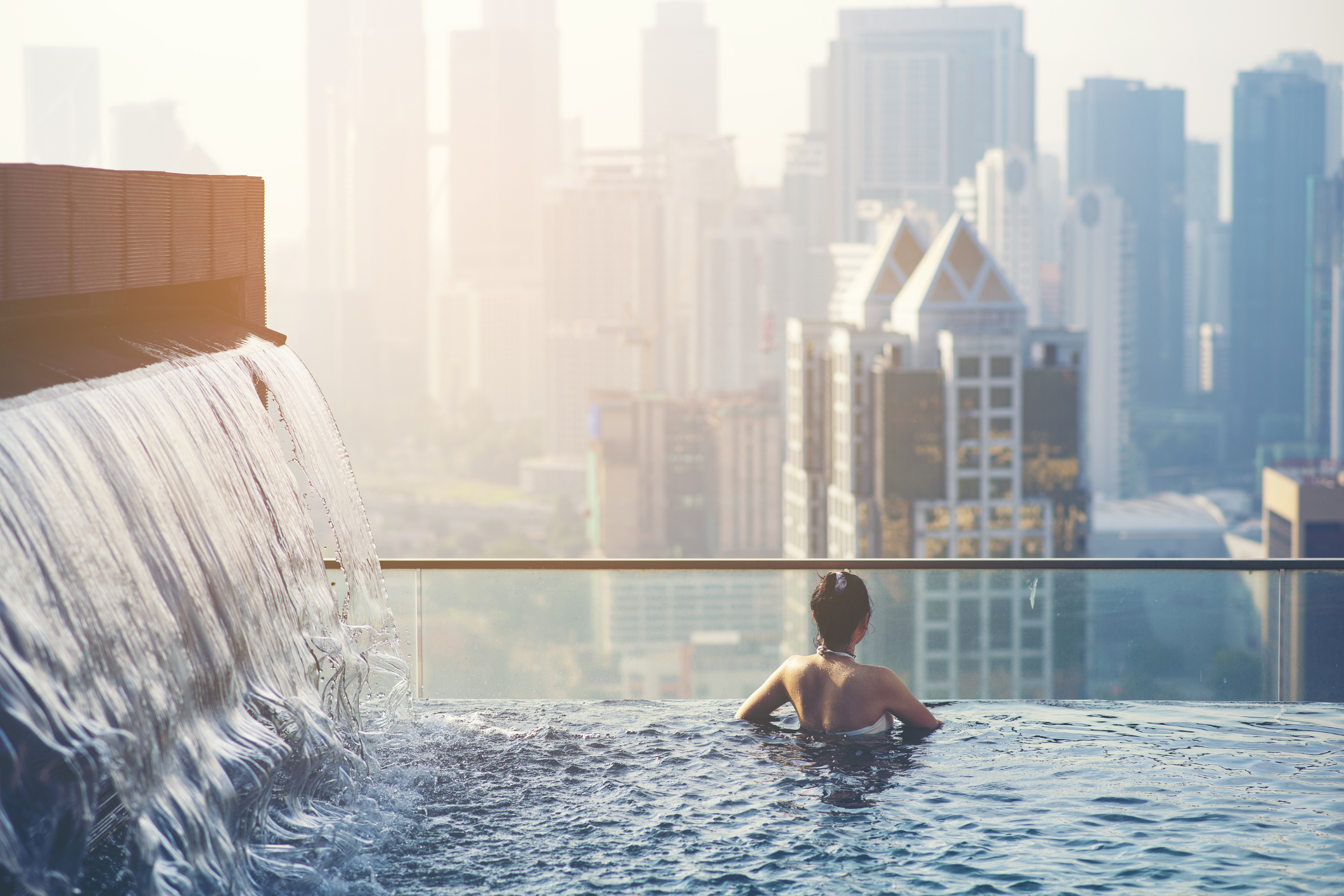 A woman in rooftop pool overlooking a city.