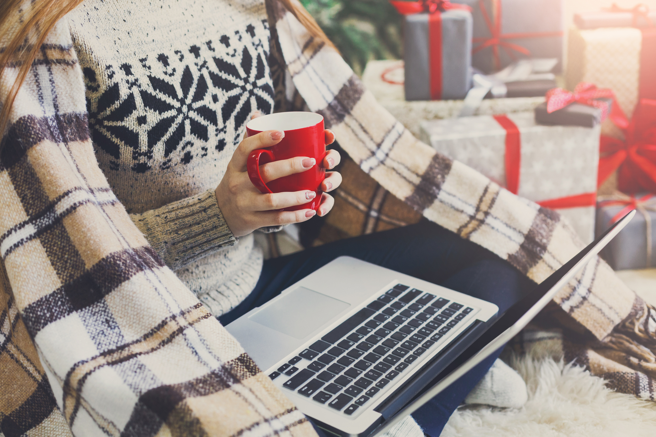 A woman holding a cup of coffee and a laptop with a blanket and presents around her.